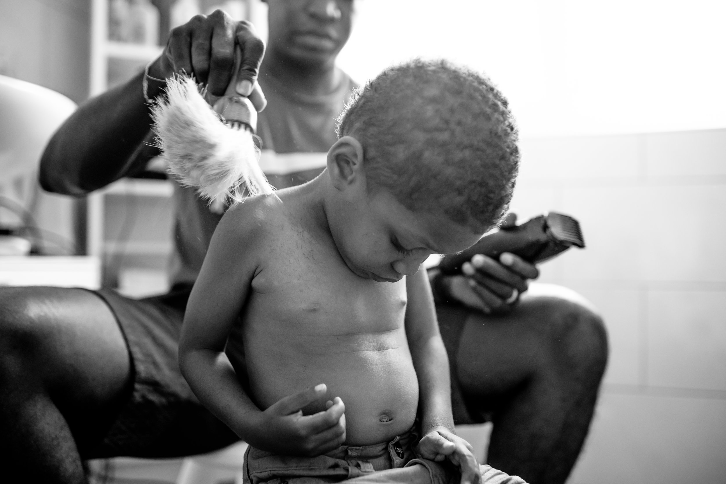 Boy looks at belly button while dad cuts his hair