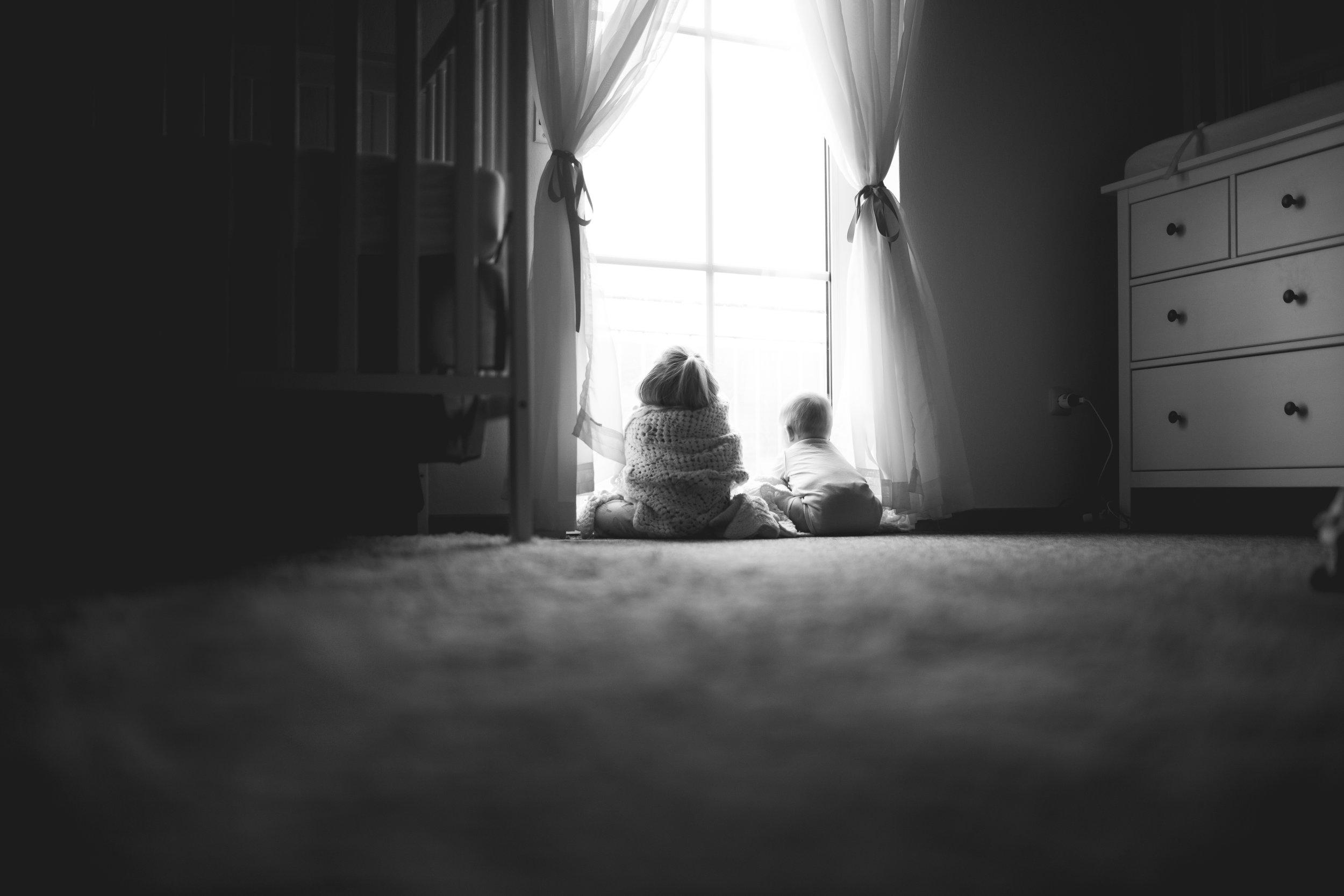 Girls sit in window of bedroom looking outside