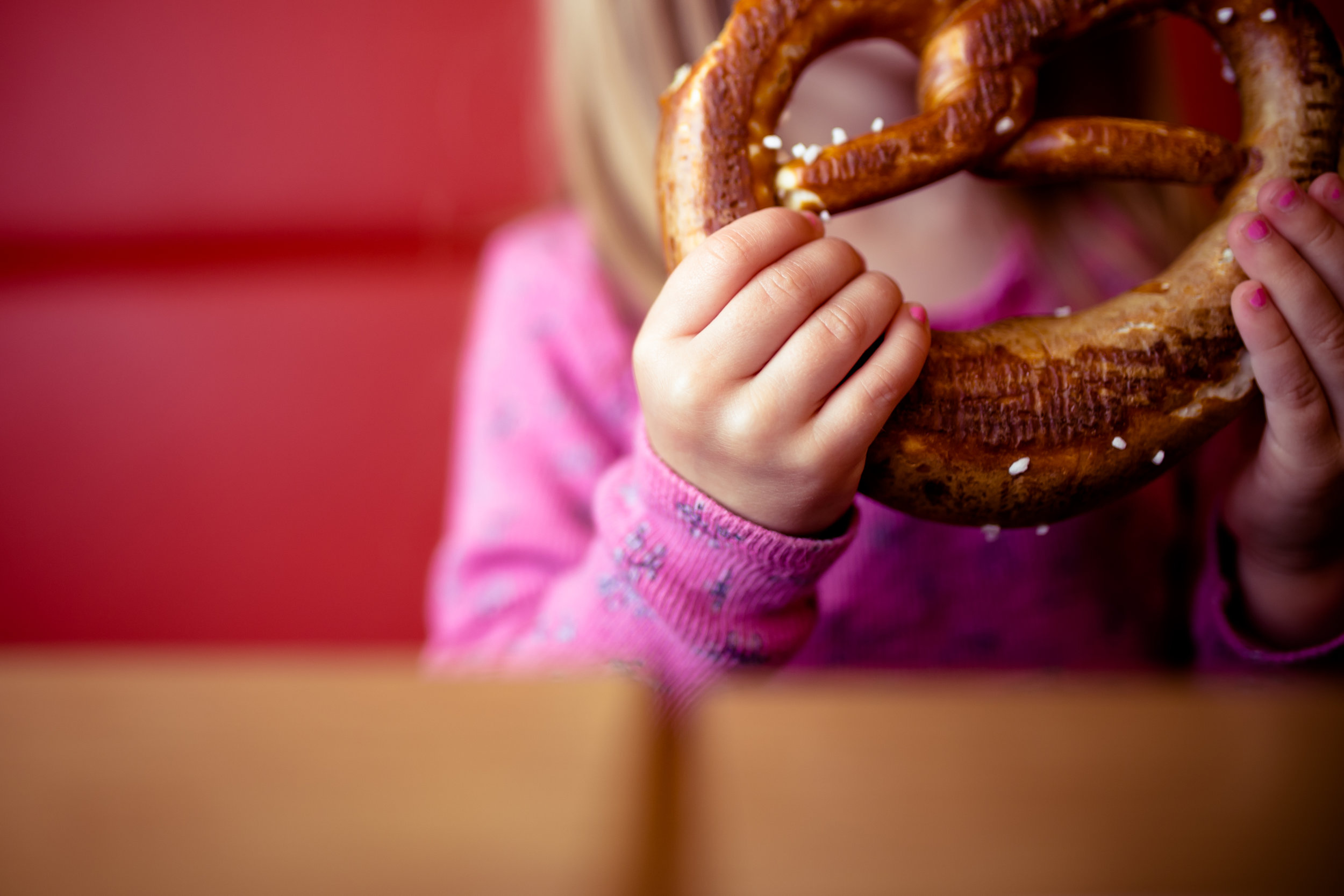girl holds salted pretzel at bakery table