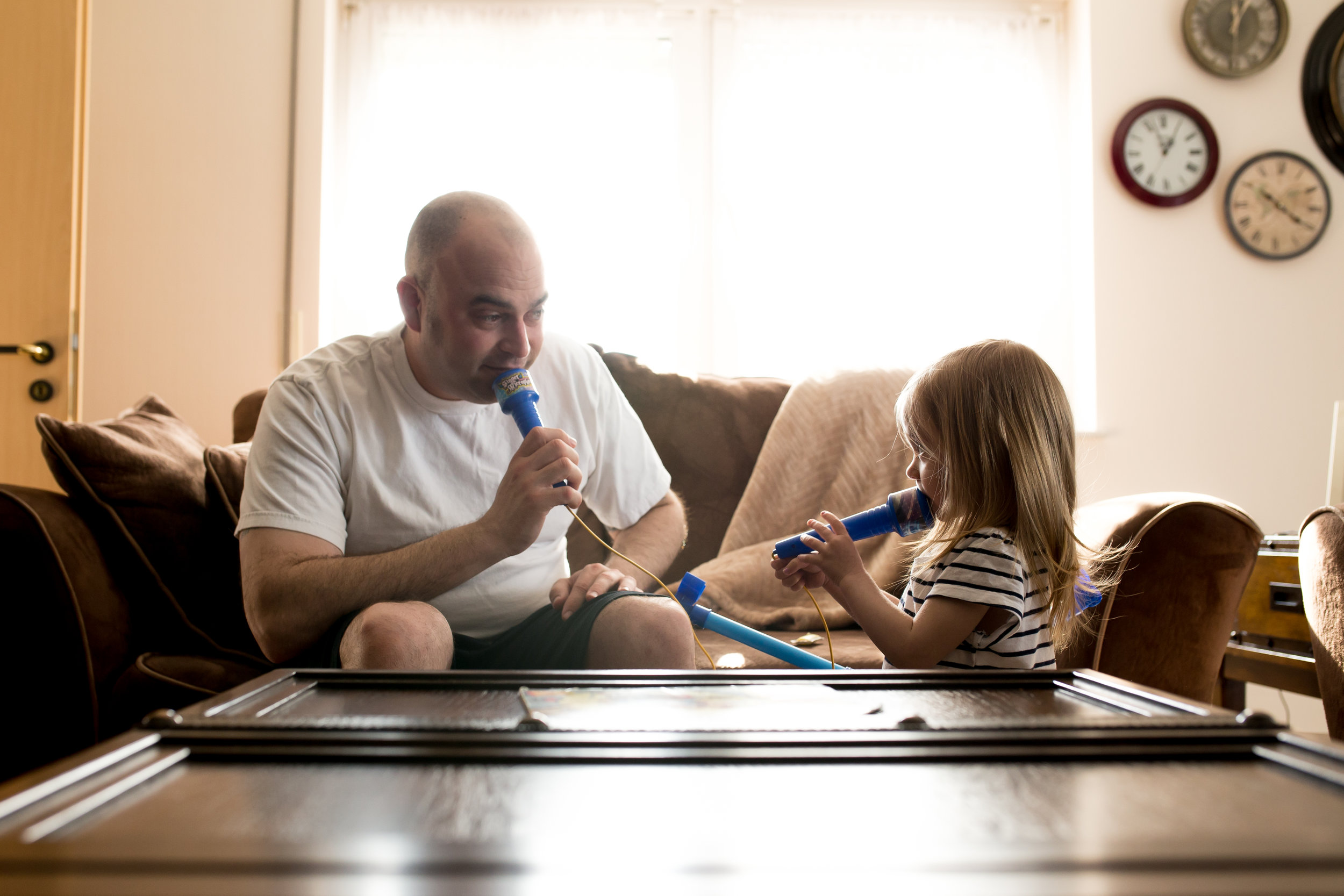 Dad and daughter sing with toy microphones in sunshine