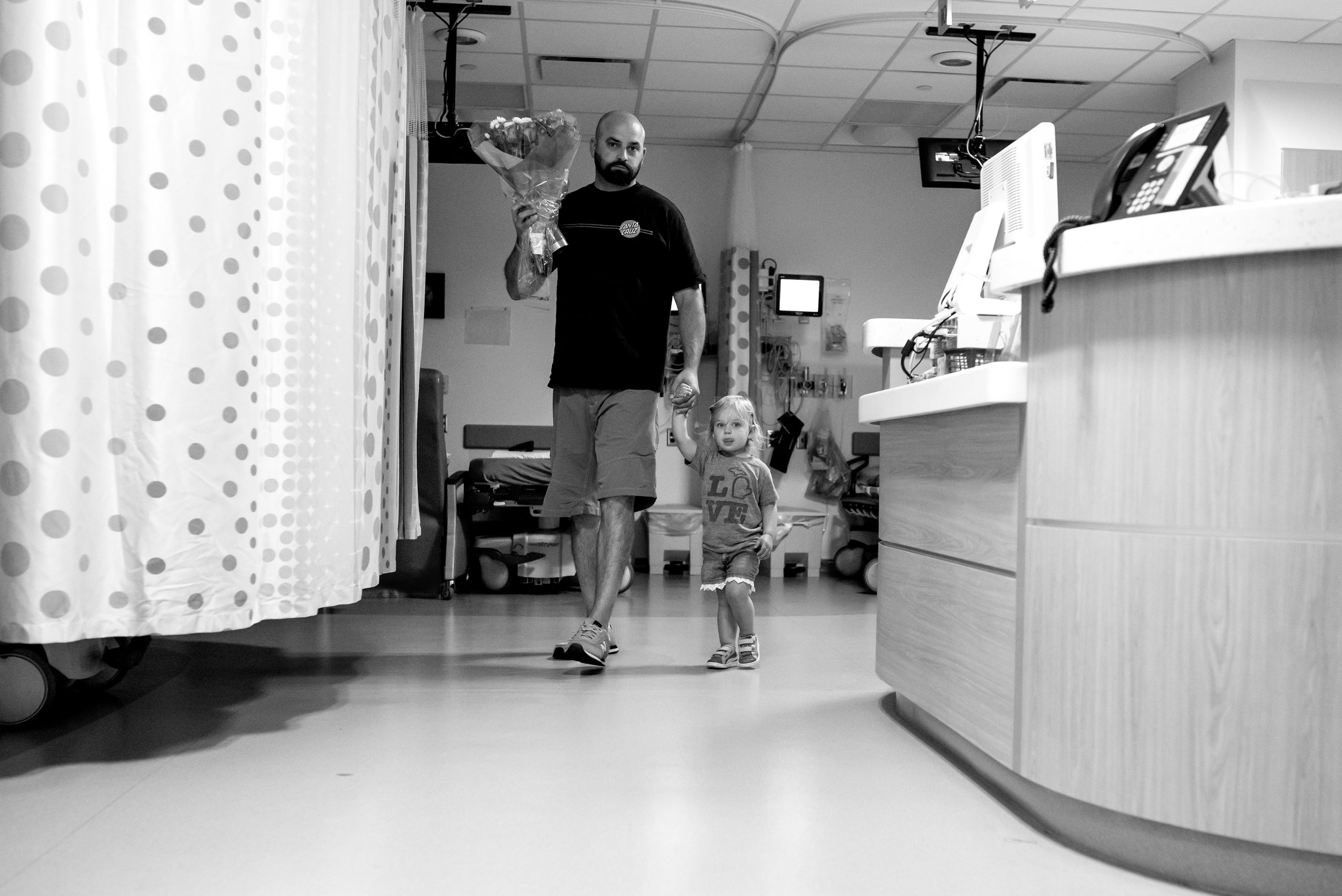 Dad and daughter bring flowers to daughter in hospital