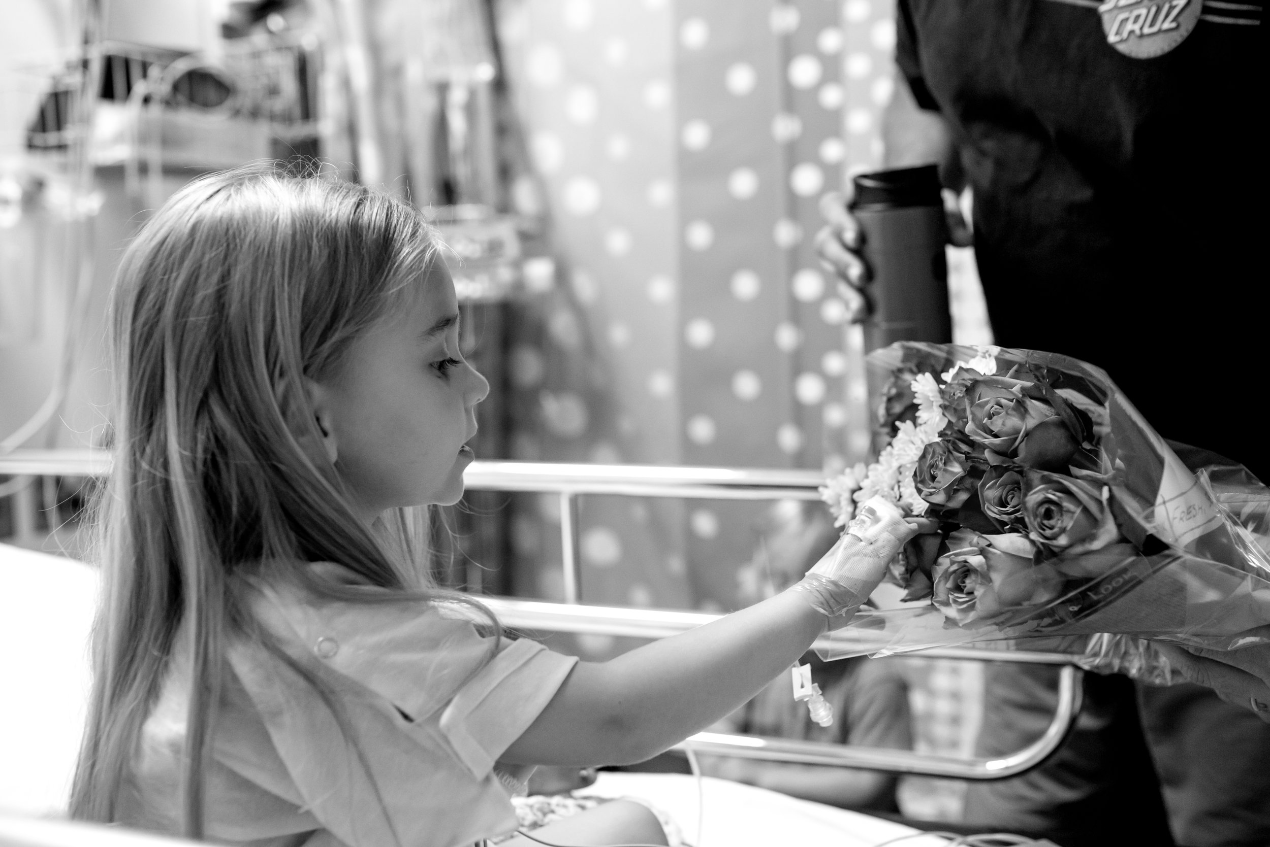 Girl touches flowers in hospital
