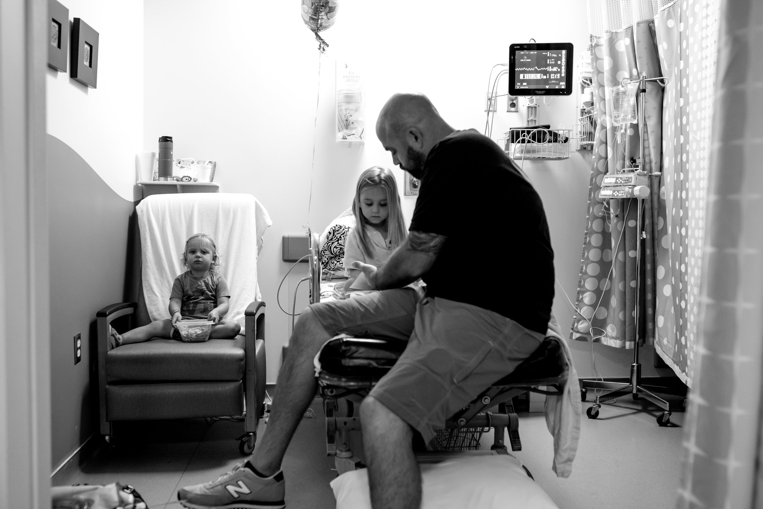 Dad and daughter look at book in hospital and girl eats snack