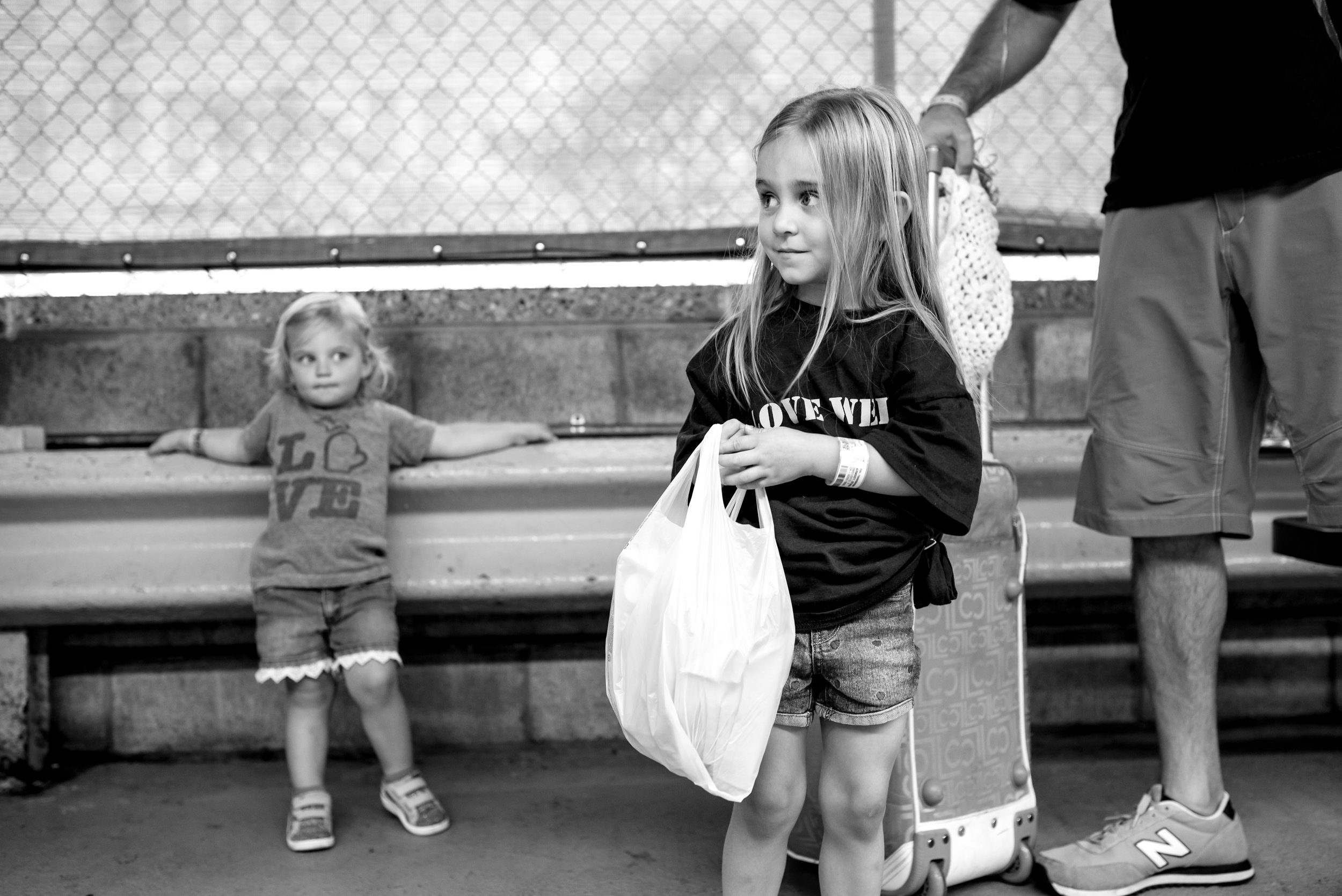 Little sister looks at big sister while family waits for car