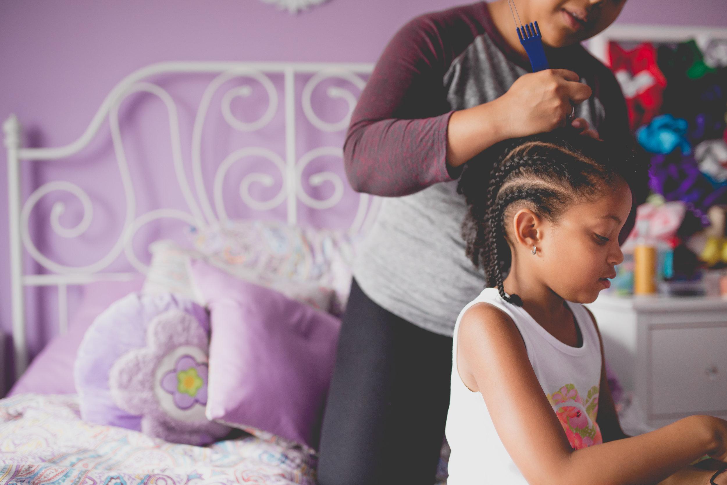 Mom puts cornrows in daughter's hair
