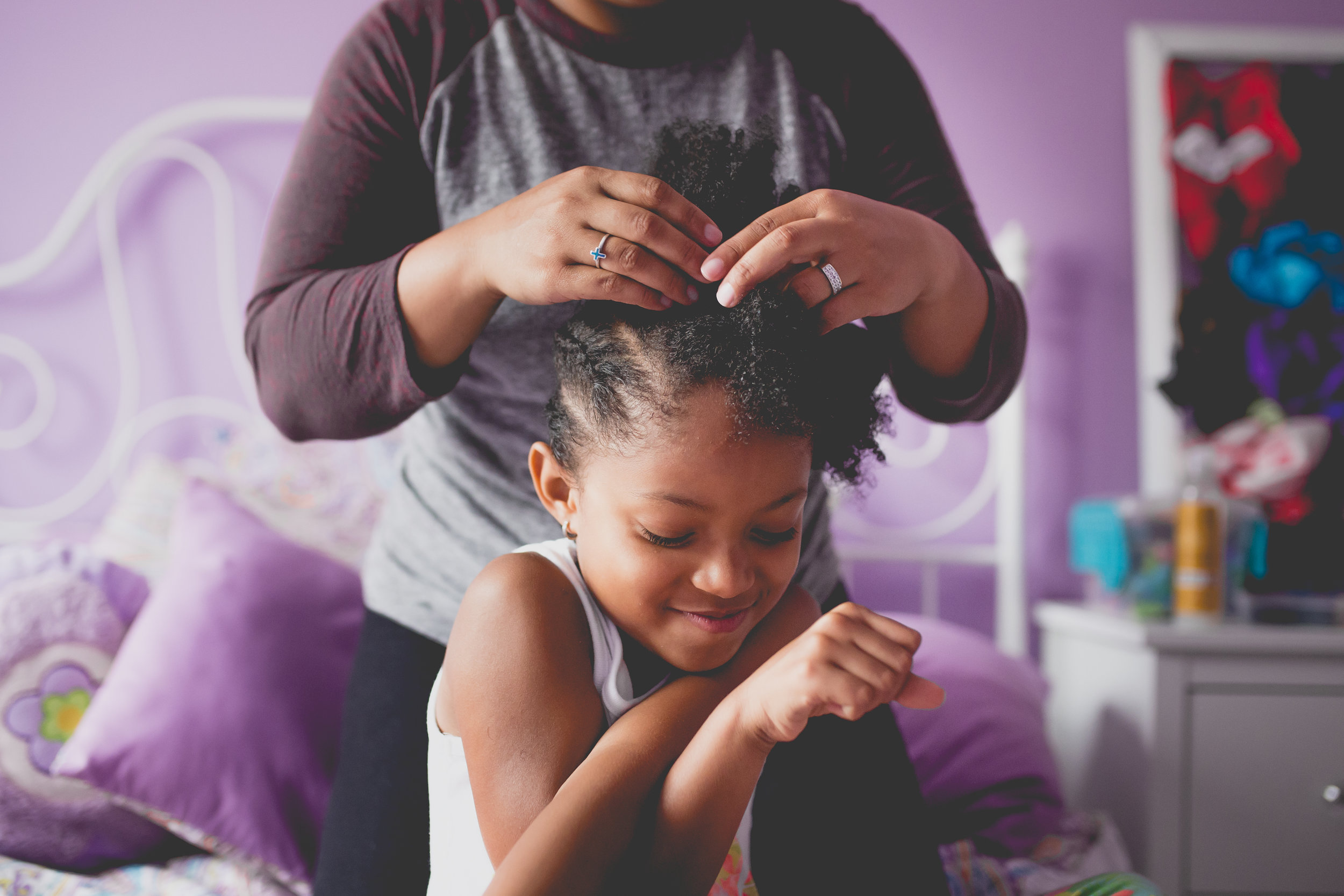 Daughter smiles while Mom puts cornrows in her hair