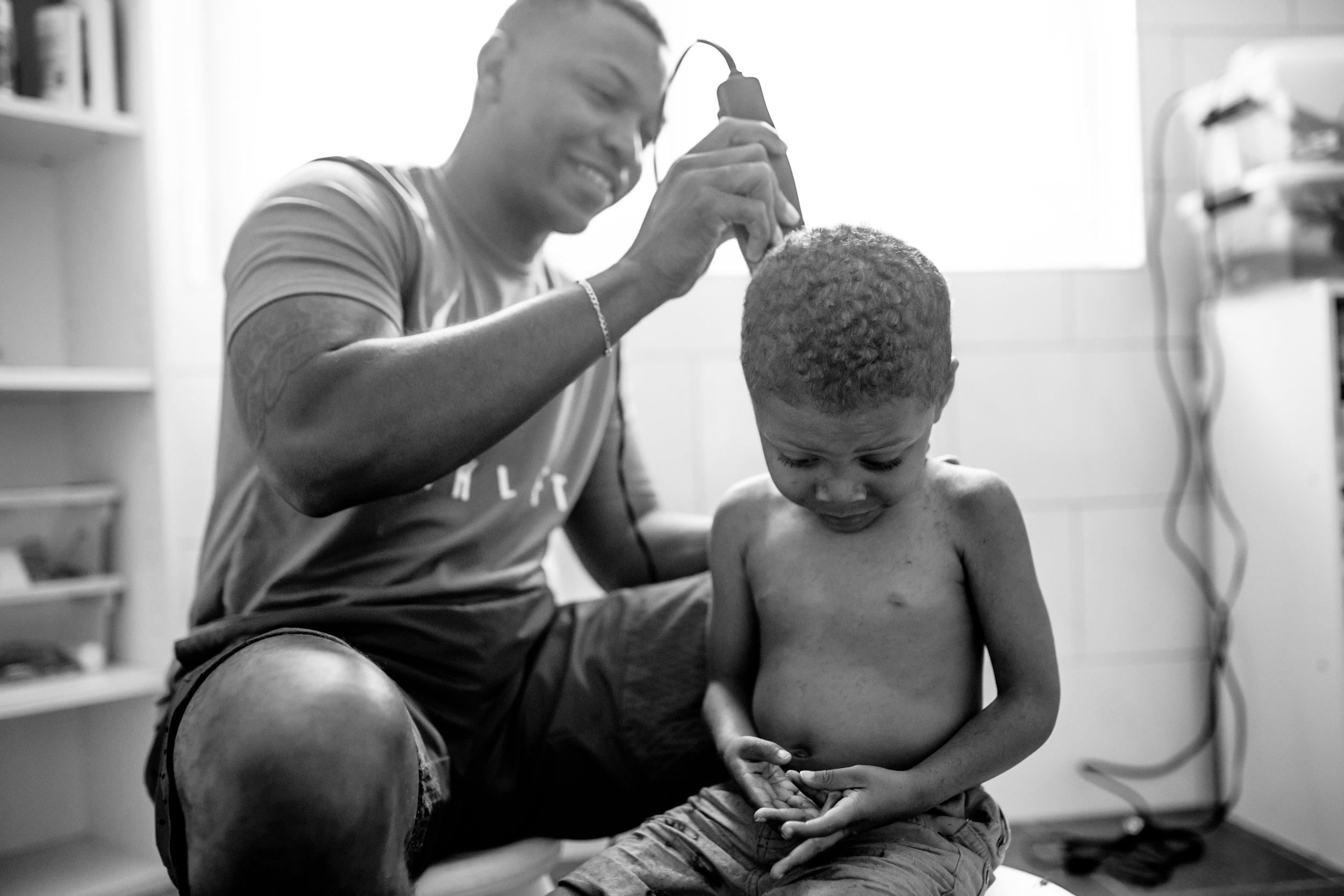 Dad smiles and cuts back of son's hair