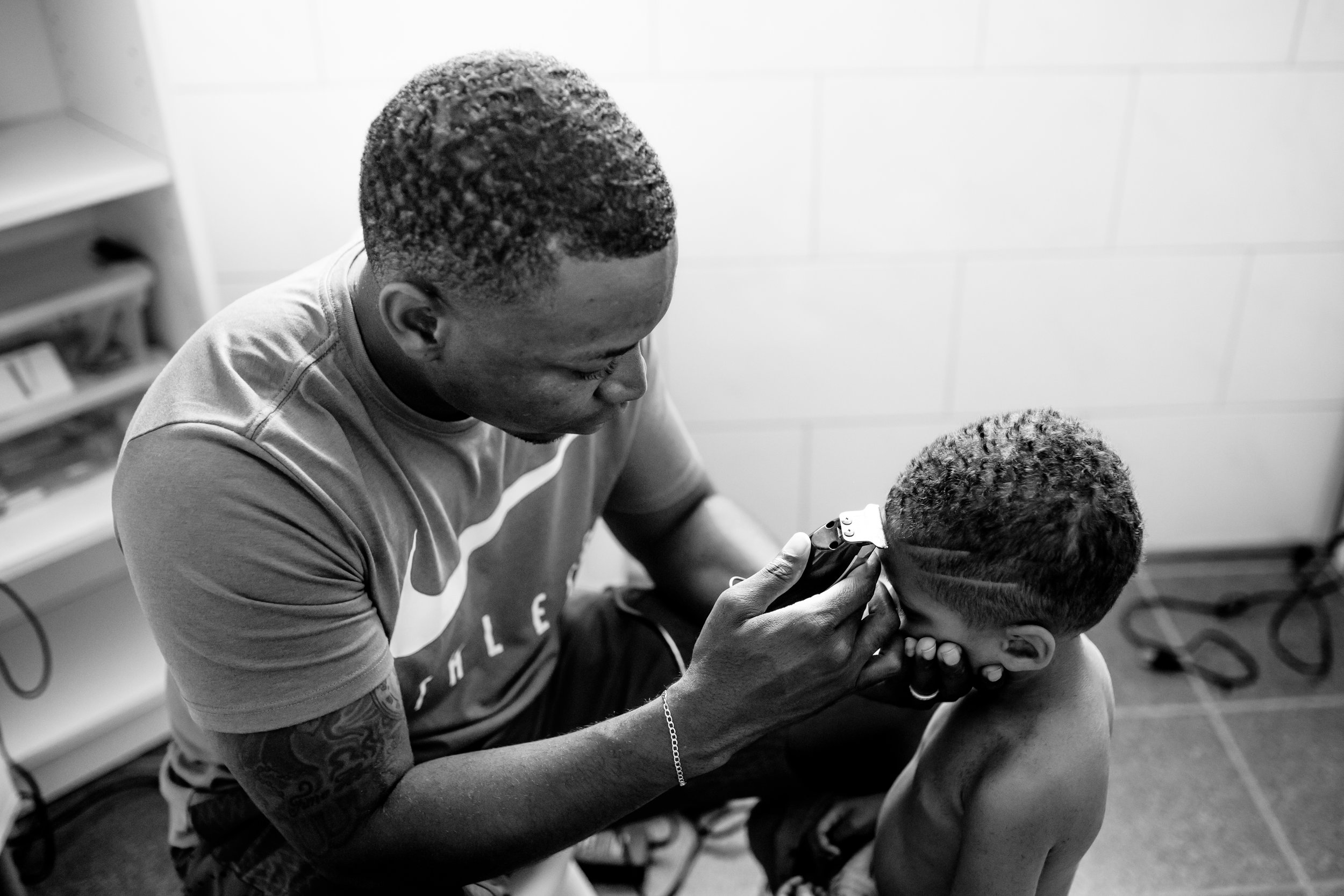 Dad cuts front of son's hair