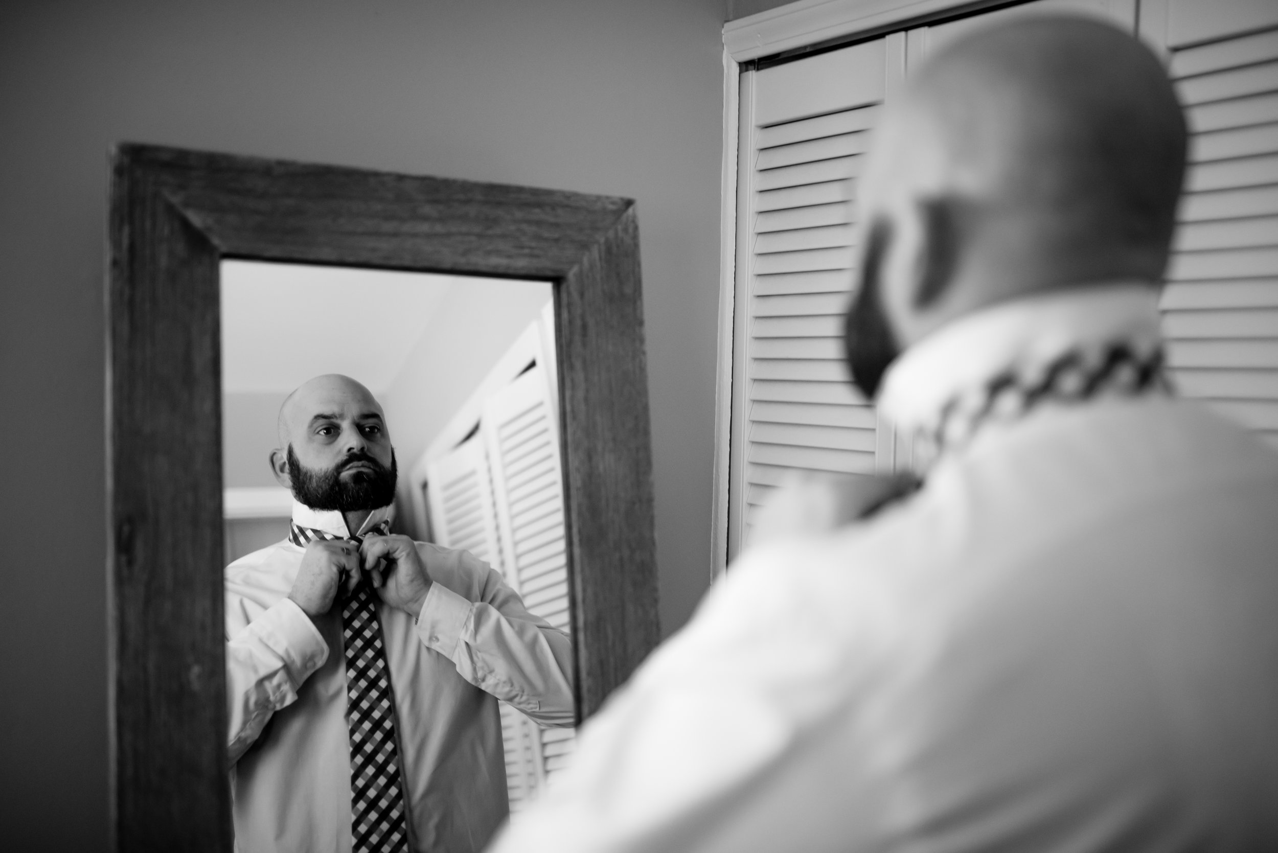 Man ties tie in mirror