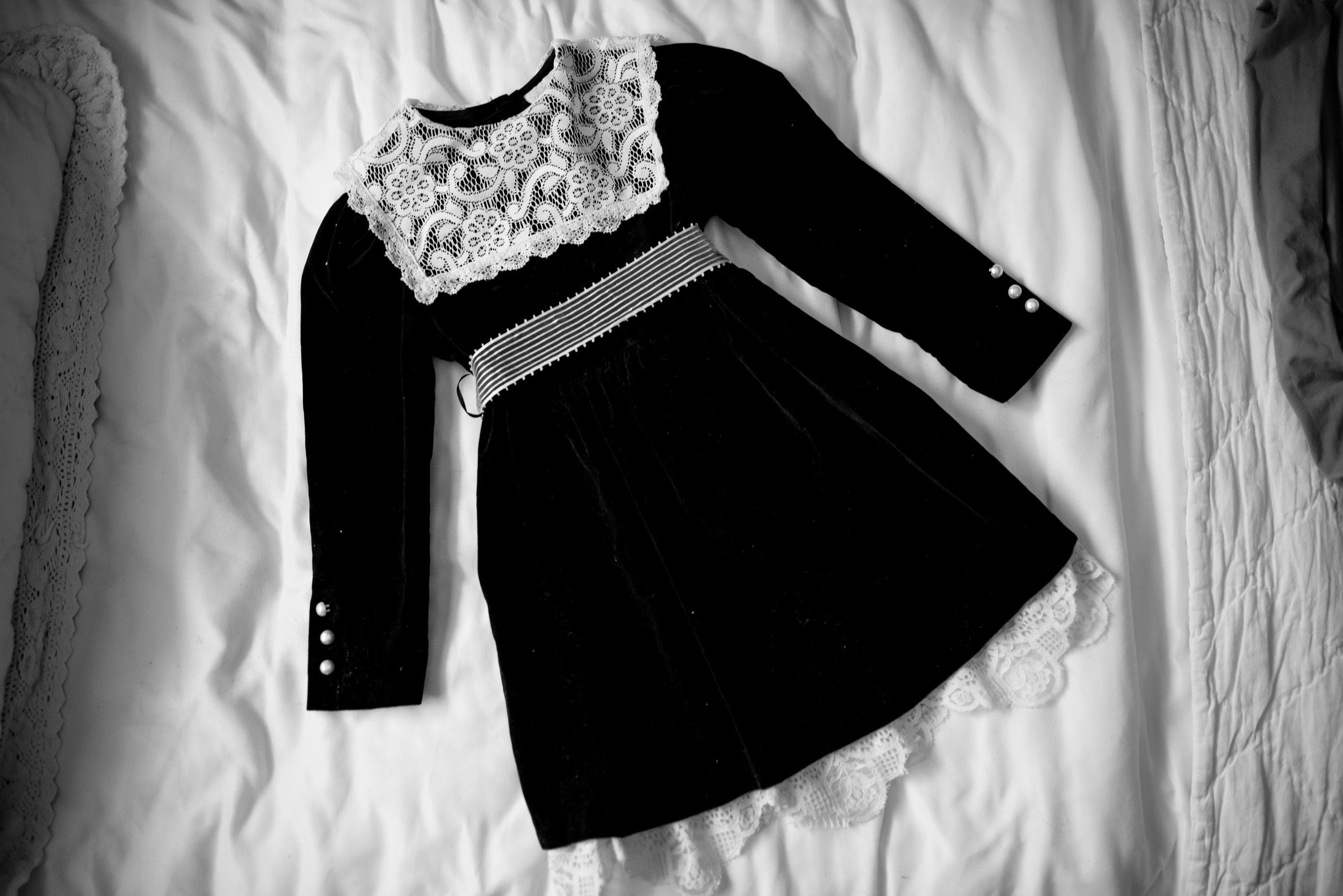 Black and white lace vintage dress sitting on bed