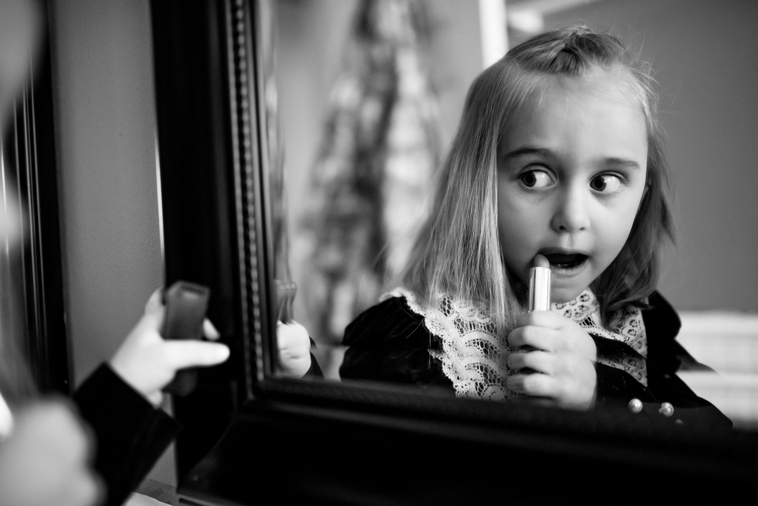 Girl applies lipstick while looking at herself in mirror