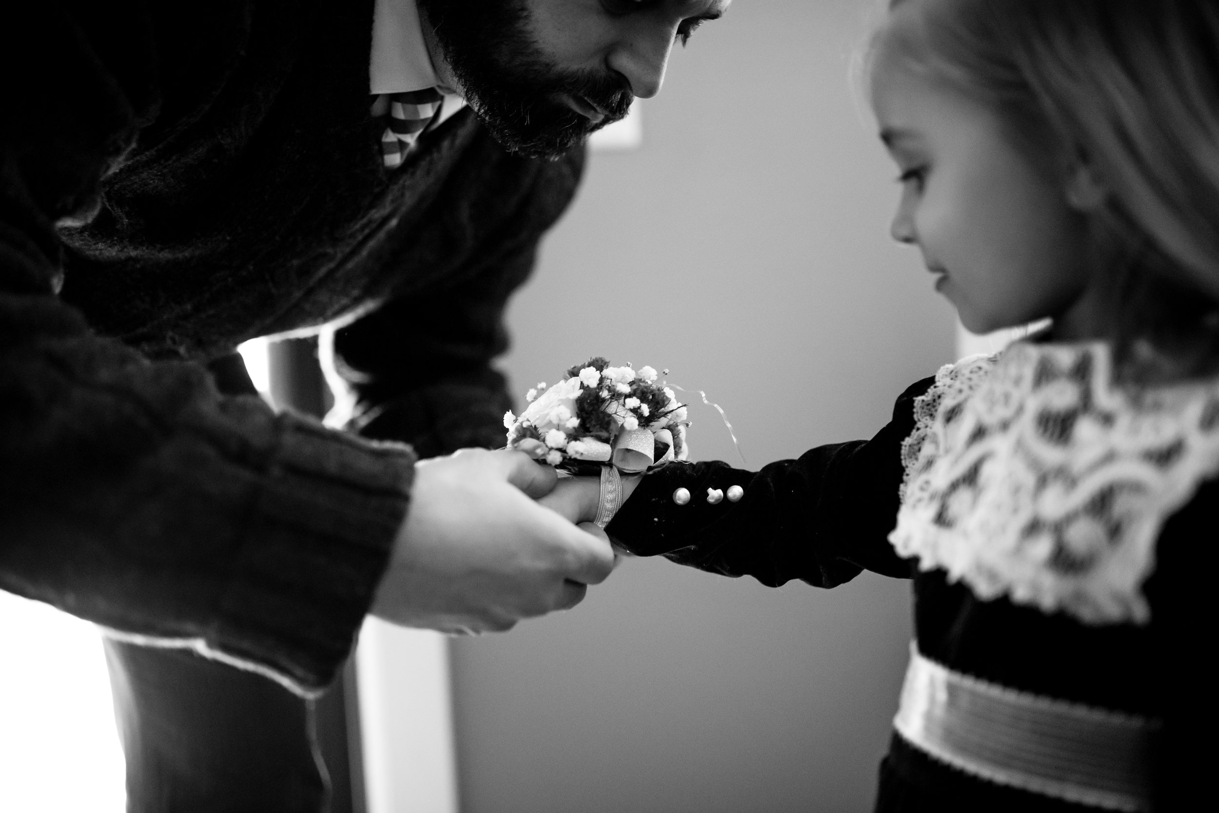 Daughter smiles at corsage as Dad puts it on her wrist