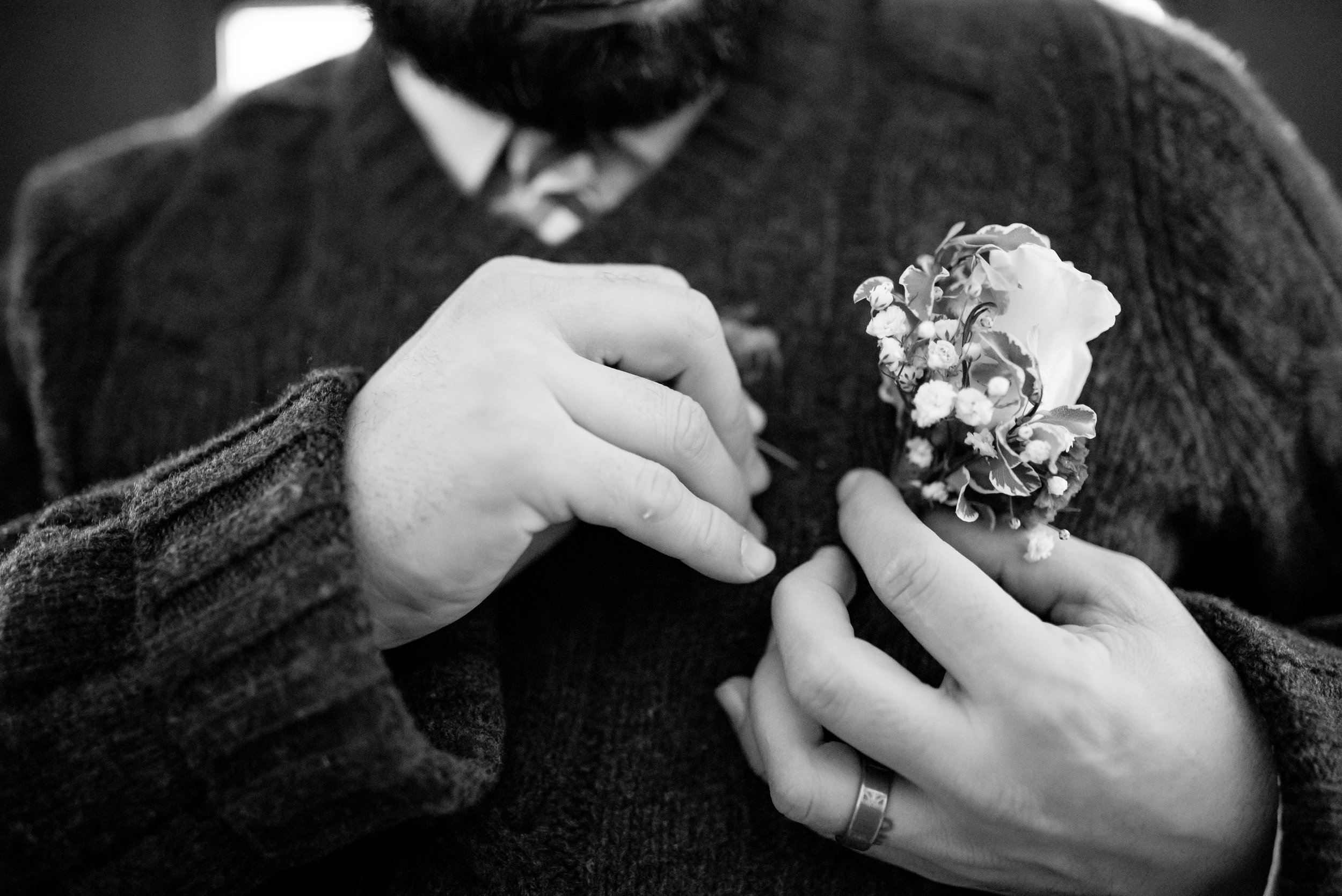 Man pins boutonnière on sweater