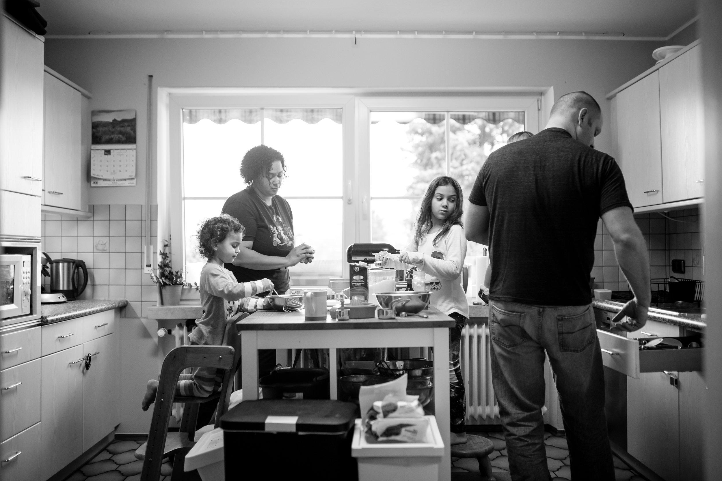 Family makes pancakes in kitchen