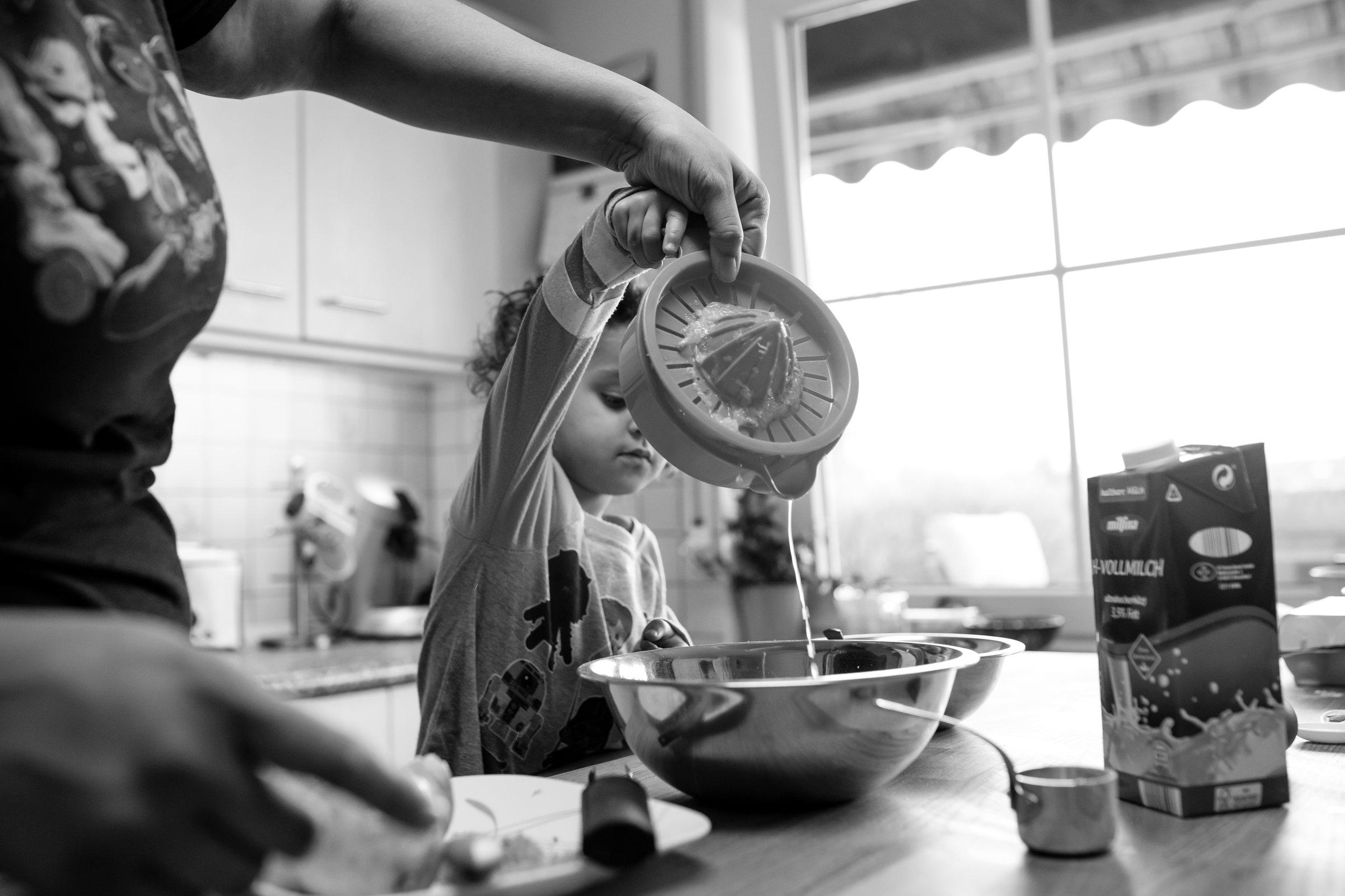 Mom helps girl pour lemon juice into pancake mix