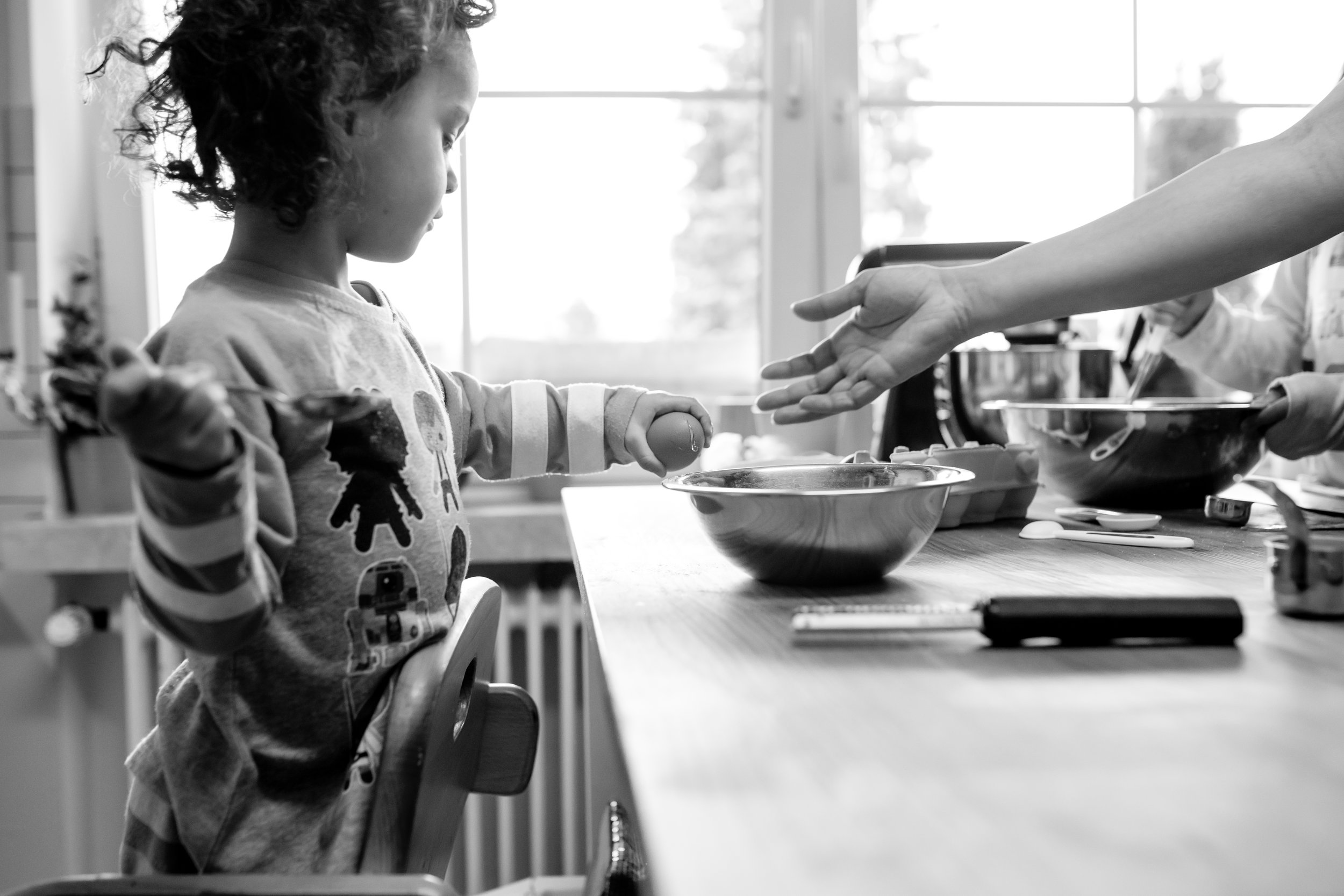 Girl cracks egg on bowl and Mom reaches for it