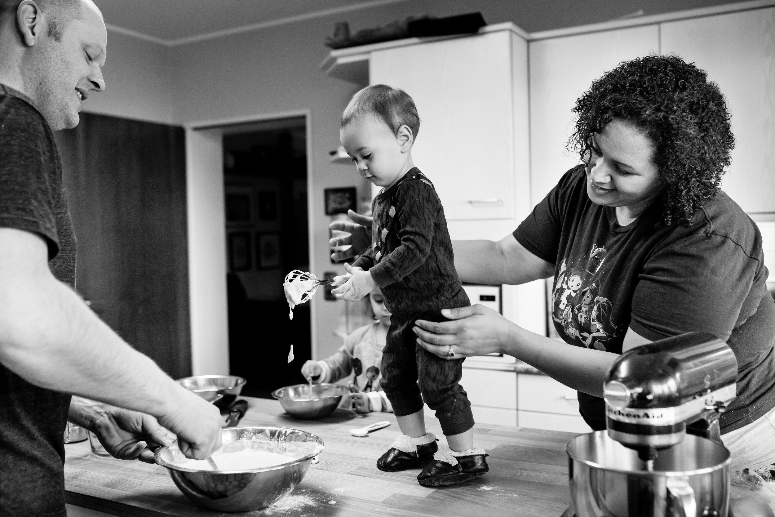 Parents help son mix pancake batter