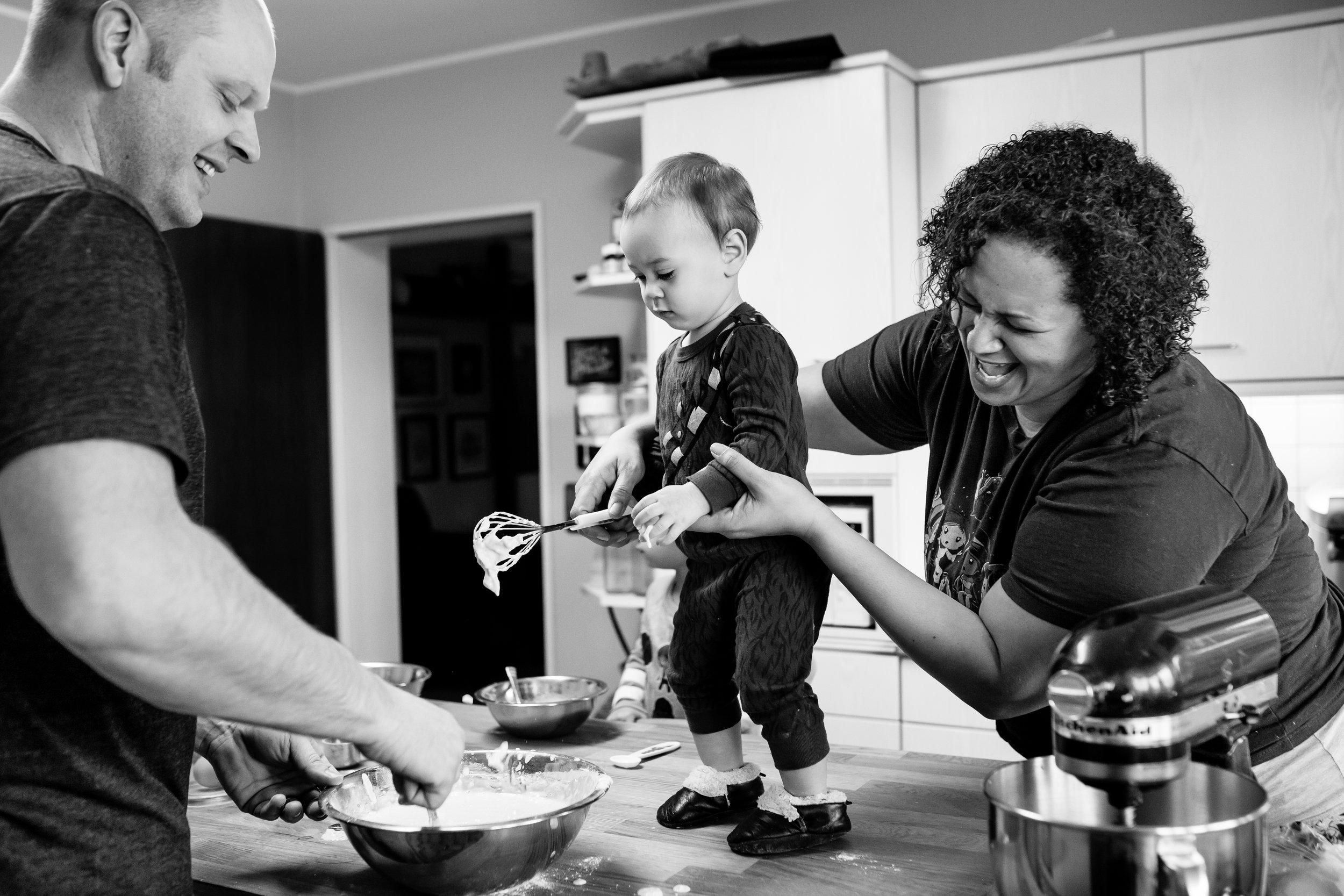 Mom and Dad laugh as baby makes mess mixing pancake batter