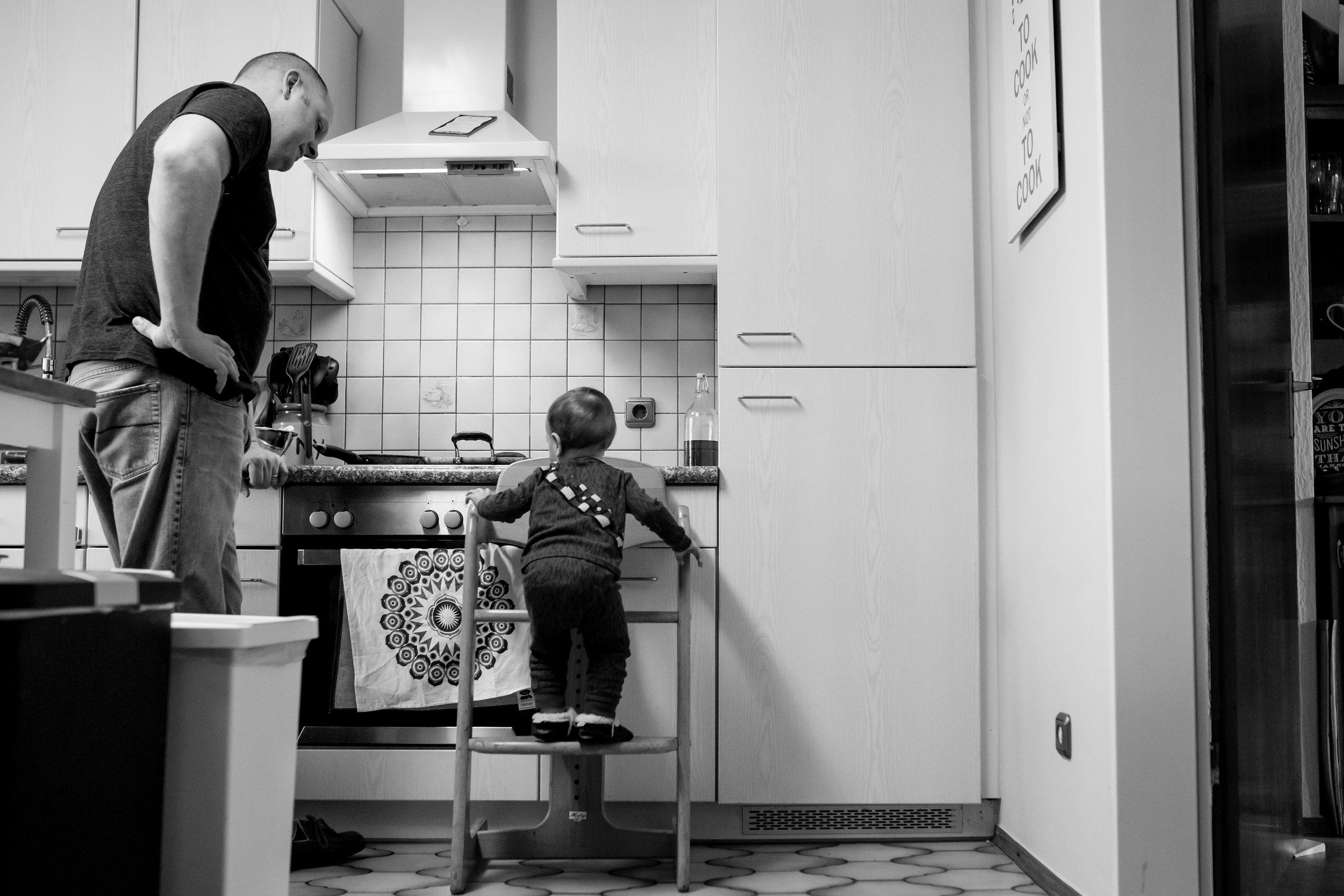 Boy climbs onto stool to help Dad cook