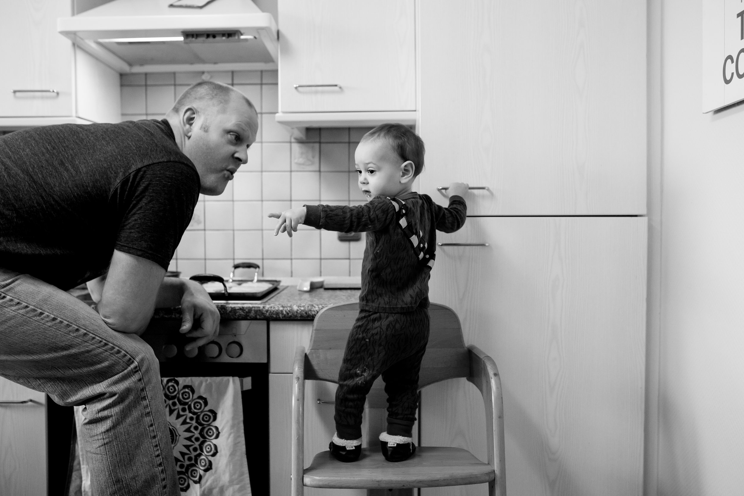 Son on stool points and Dad talks to him