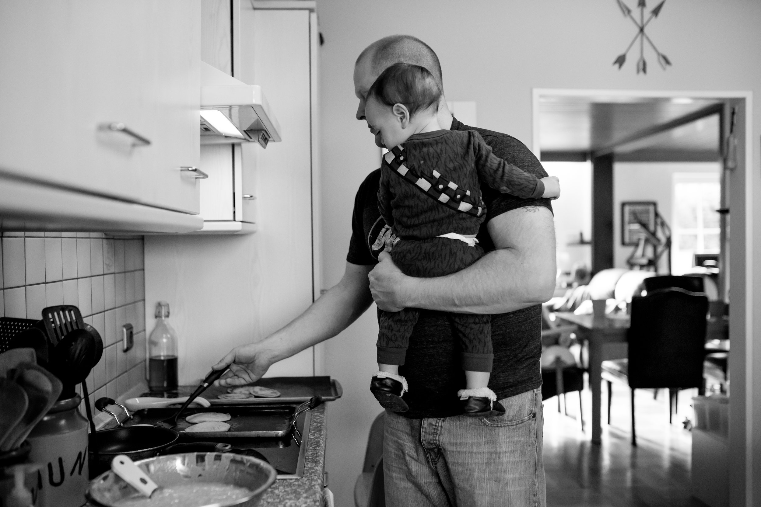 Dad holds son while flipping pancakes