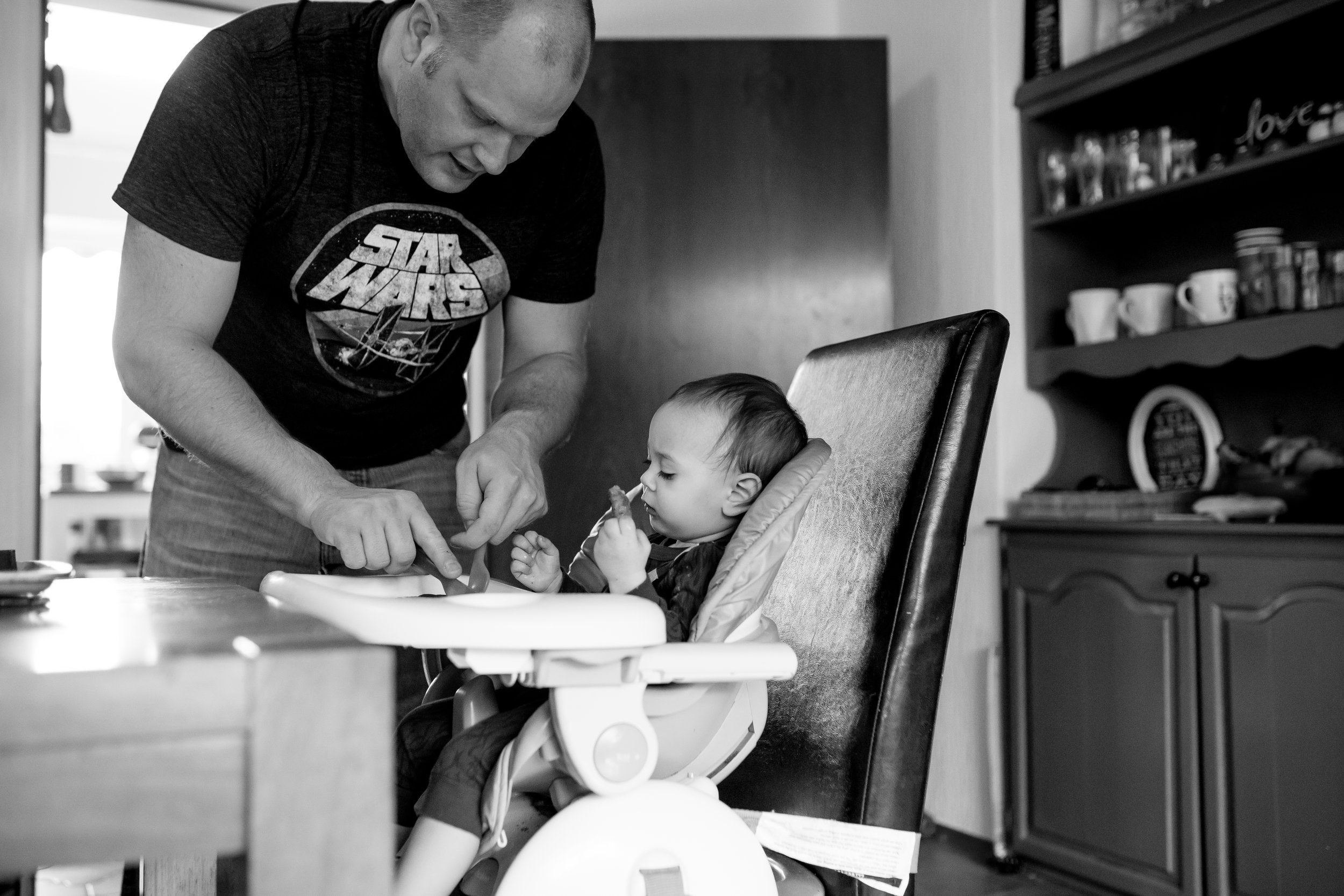 Dad cuts food for son in high chair