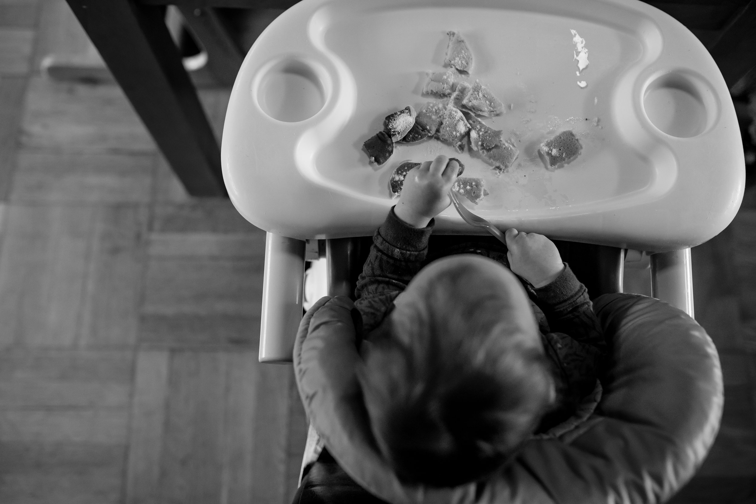 Baby eats pancakes off of high chair tray