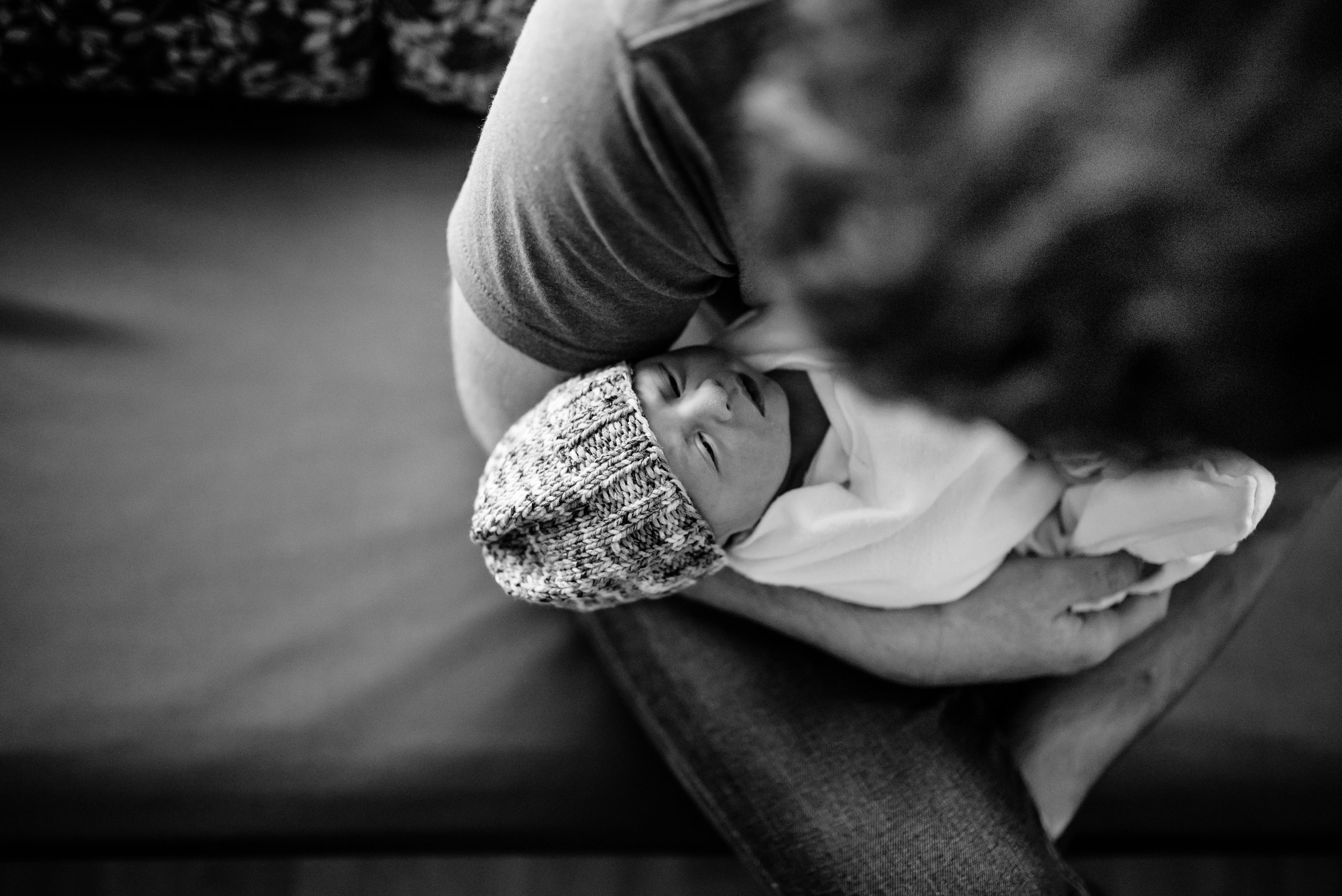 Newborn baby in dad's arms in hospital