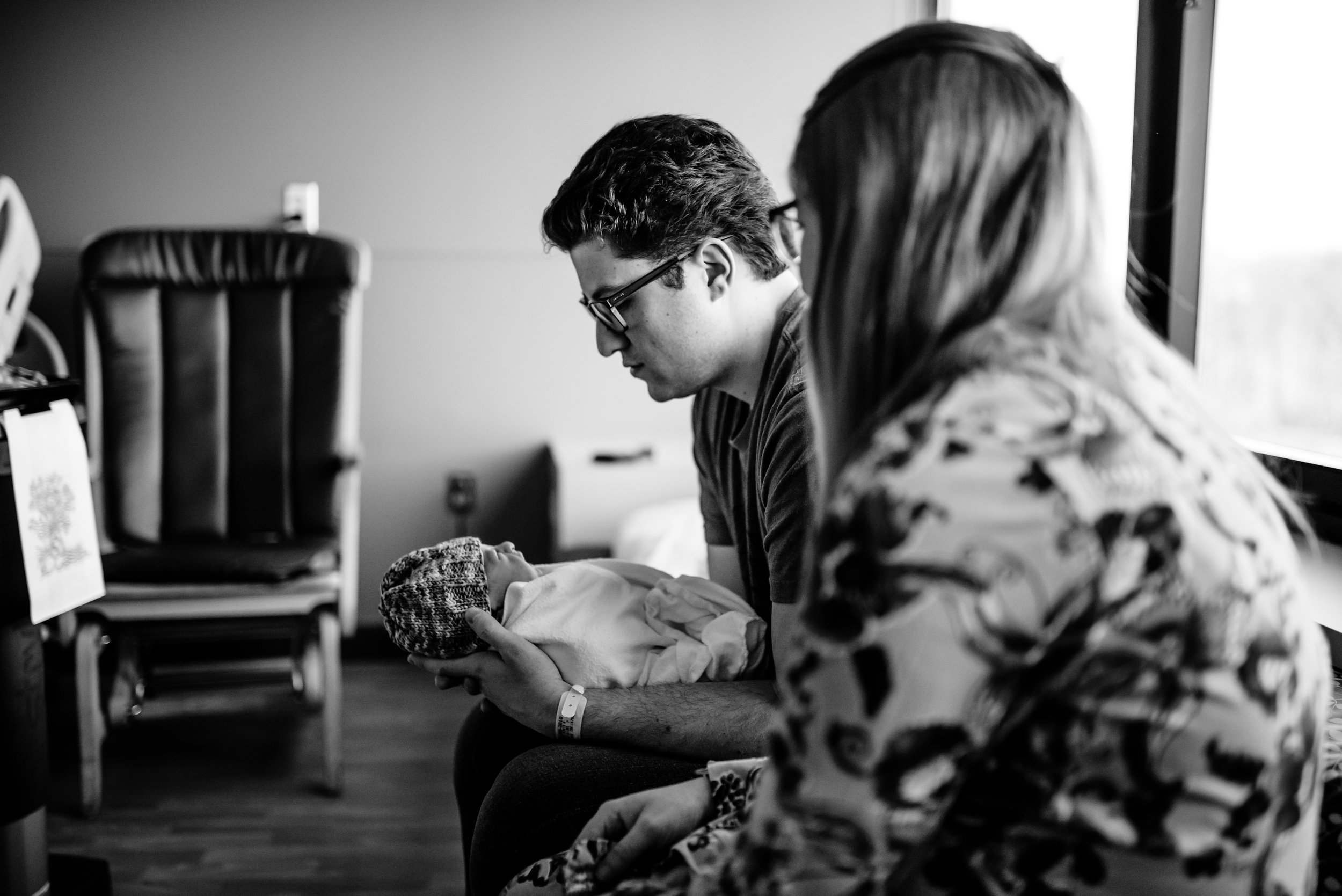 Mom looks at newborn, swaddled in Dad's arms on couch in hospital room