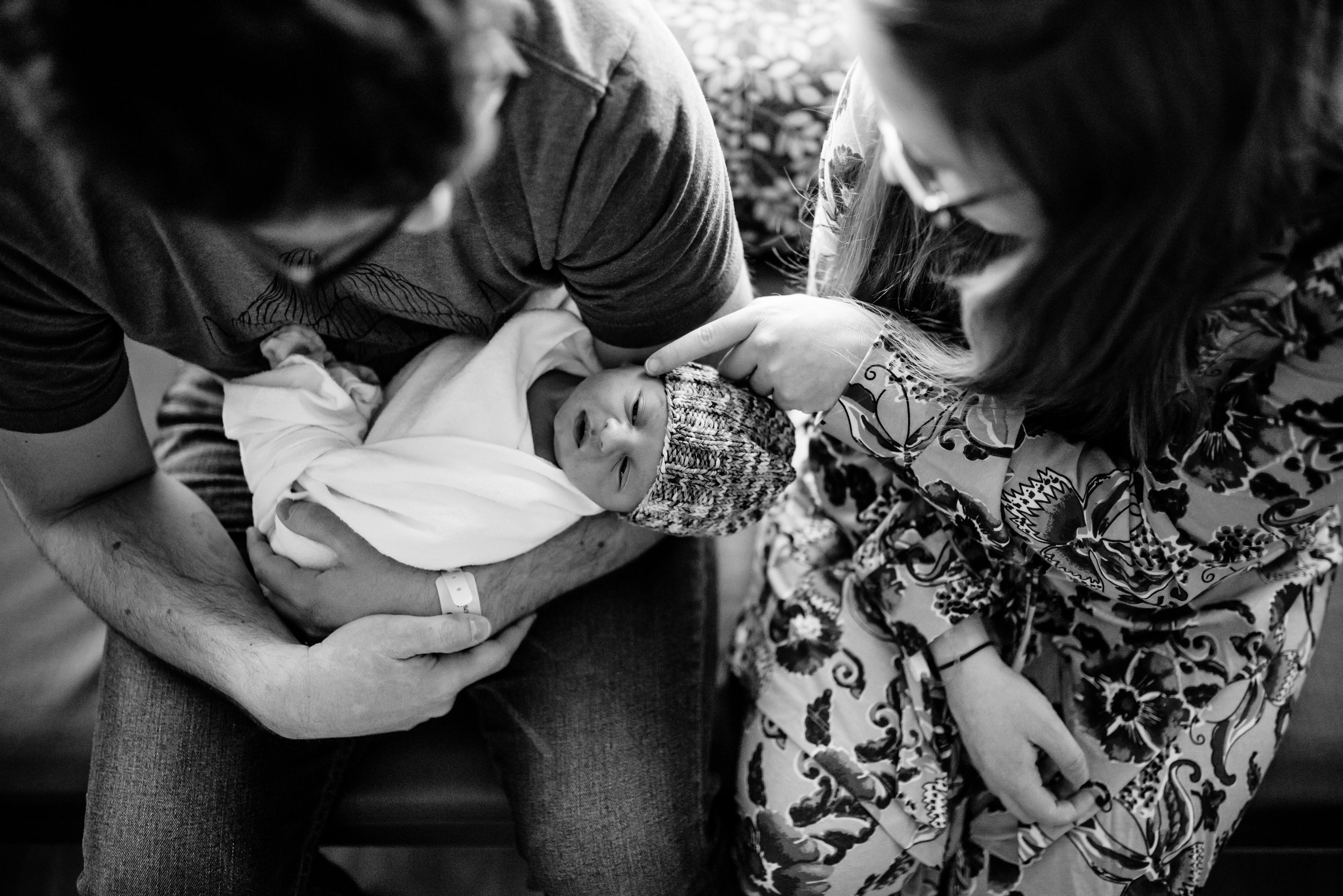 Mom and Dad look down at newborn baby; Mom touches baby's face