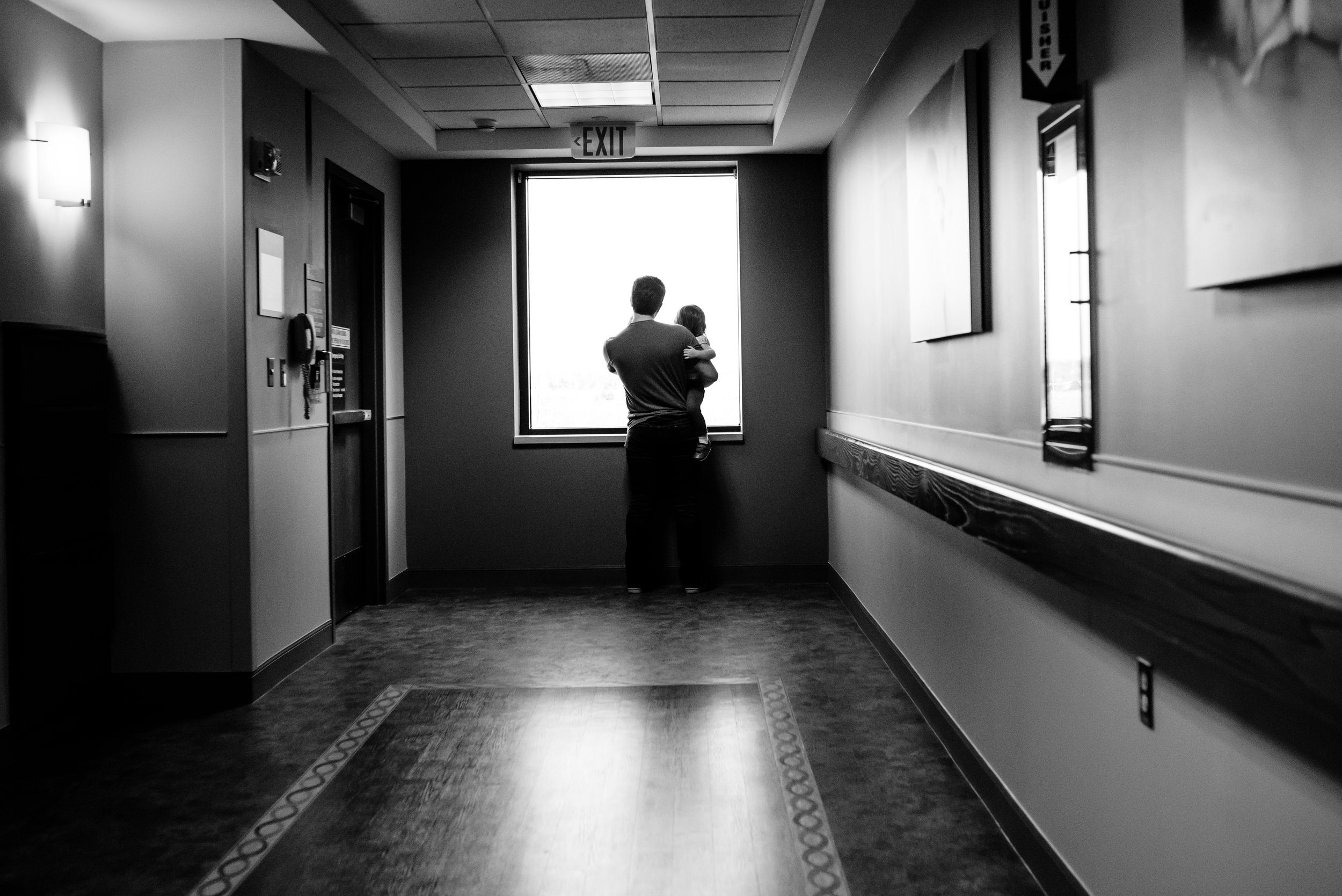 Dad holds daughter and they look outside of hospital window