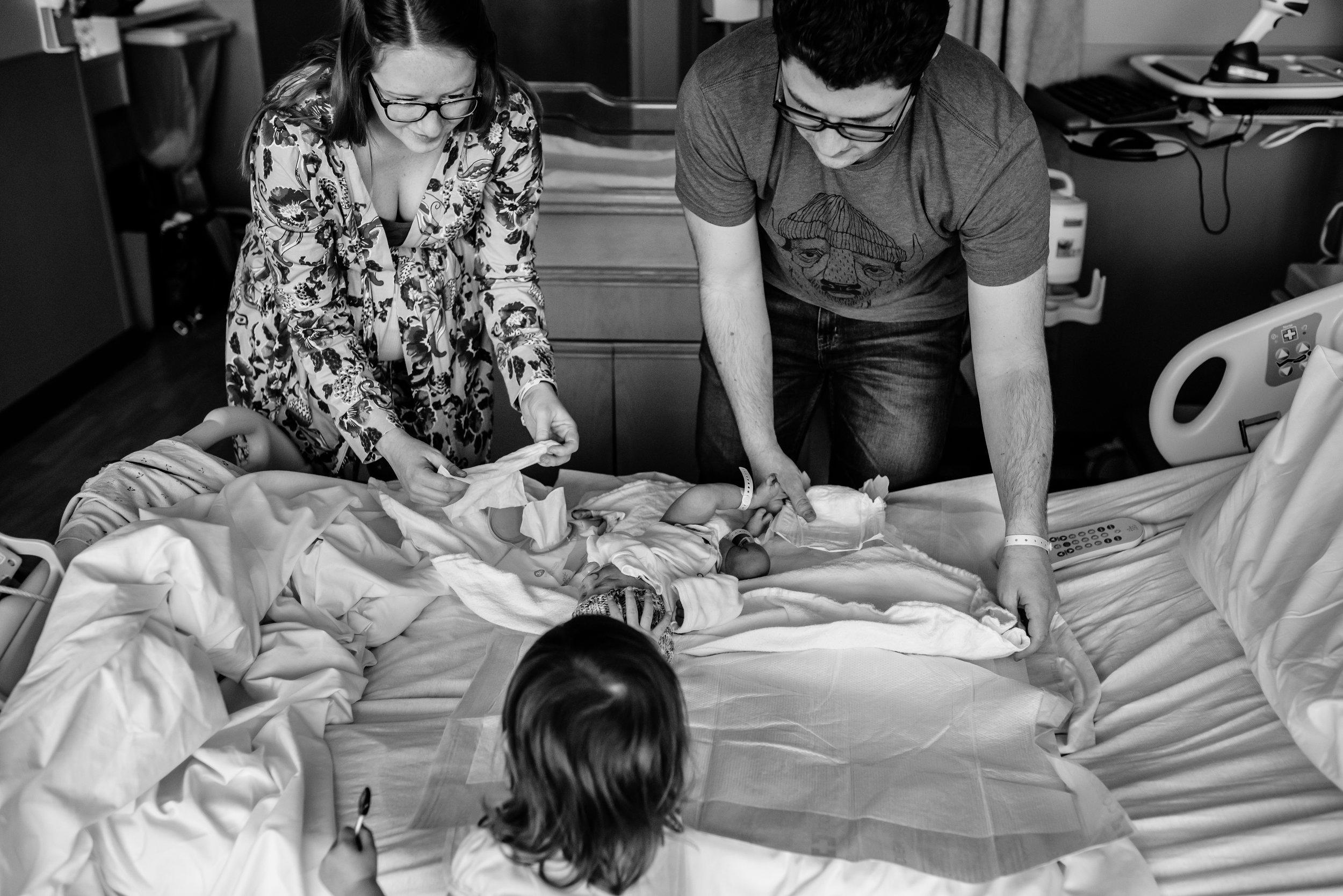 Girl helps parents change newborn brother's diaper