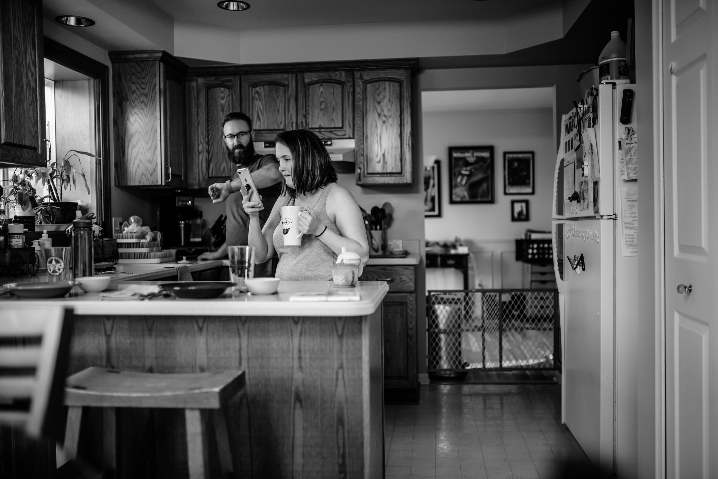 Mom and Dad in kitchen drinking coffee looking at phone and time