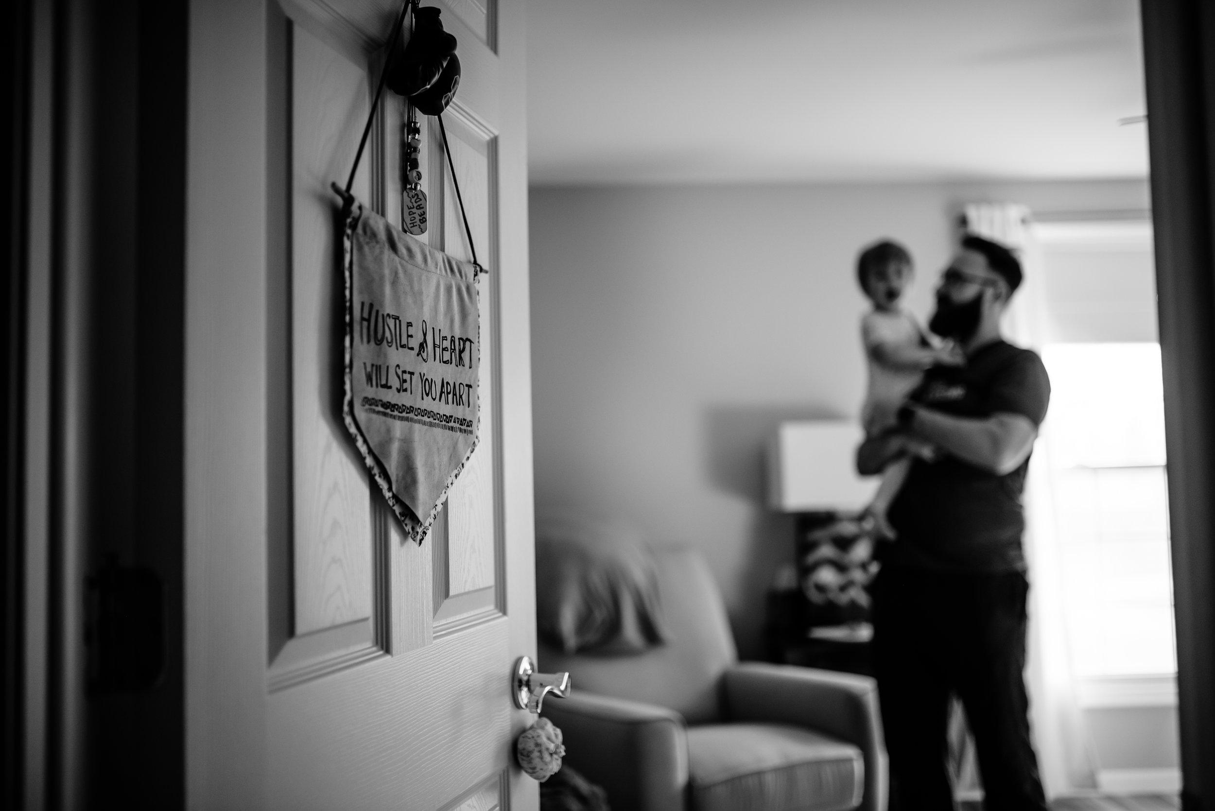 Dad holds daughter in her room, with cute sign on bedroom door