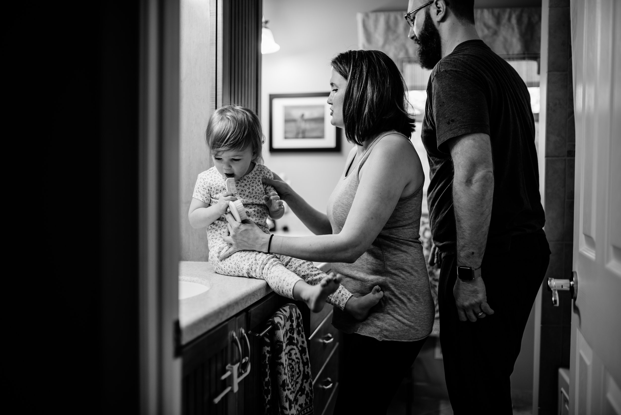 Mom and Dad get daughter ready for the day in bathroom