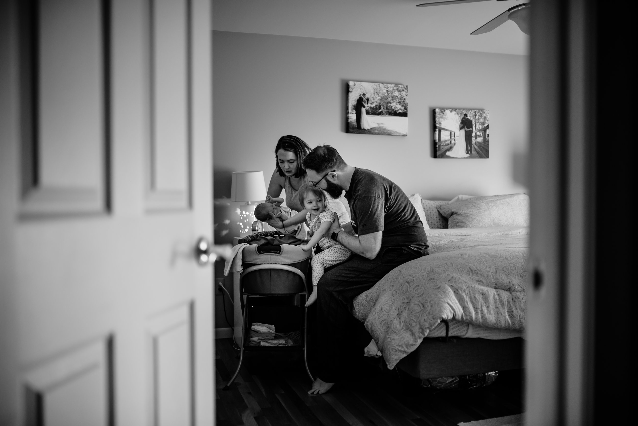 Mom and Dad hold daughters atop their bed
