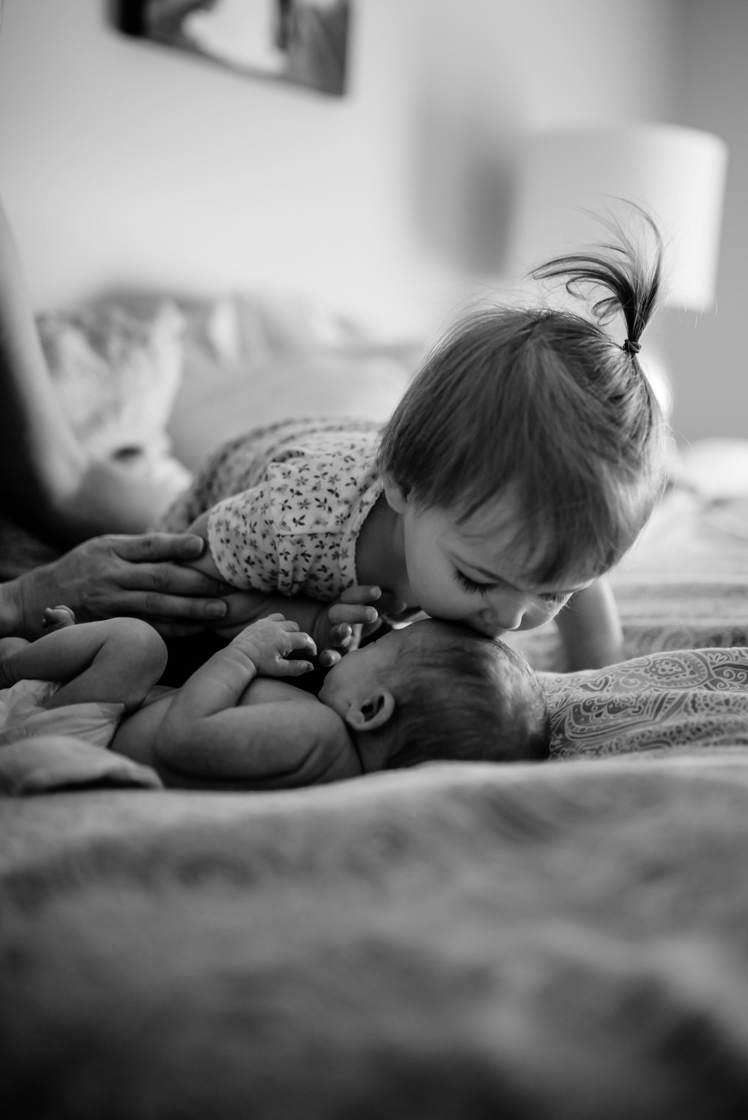 Girl kisses baby sister's head