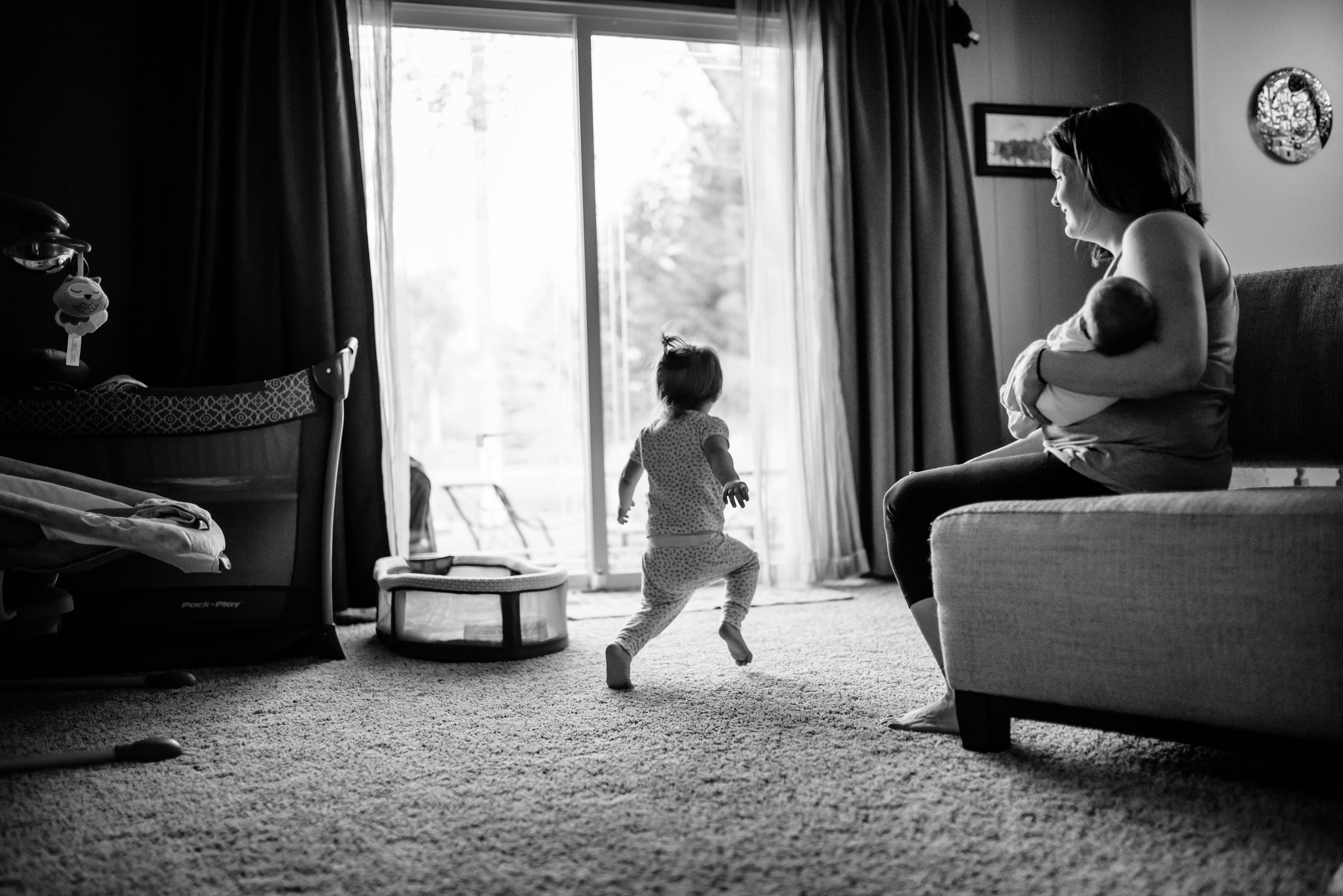 Mom holds baby and watches daughter dance