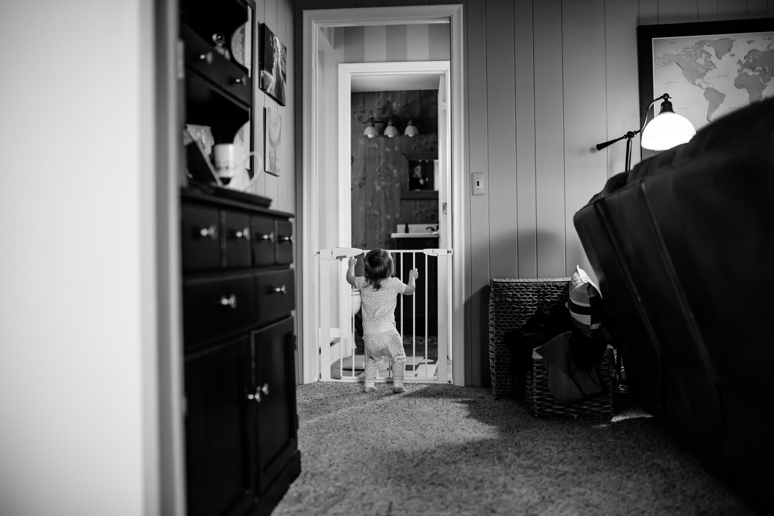 Girl stands at baby gate in doorway