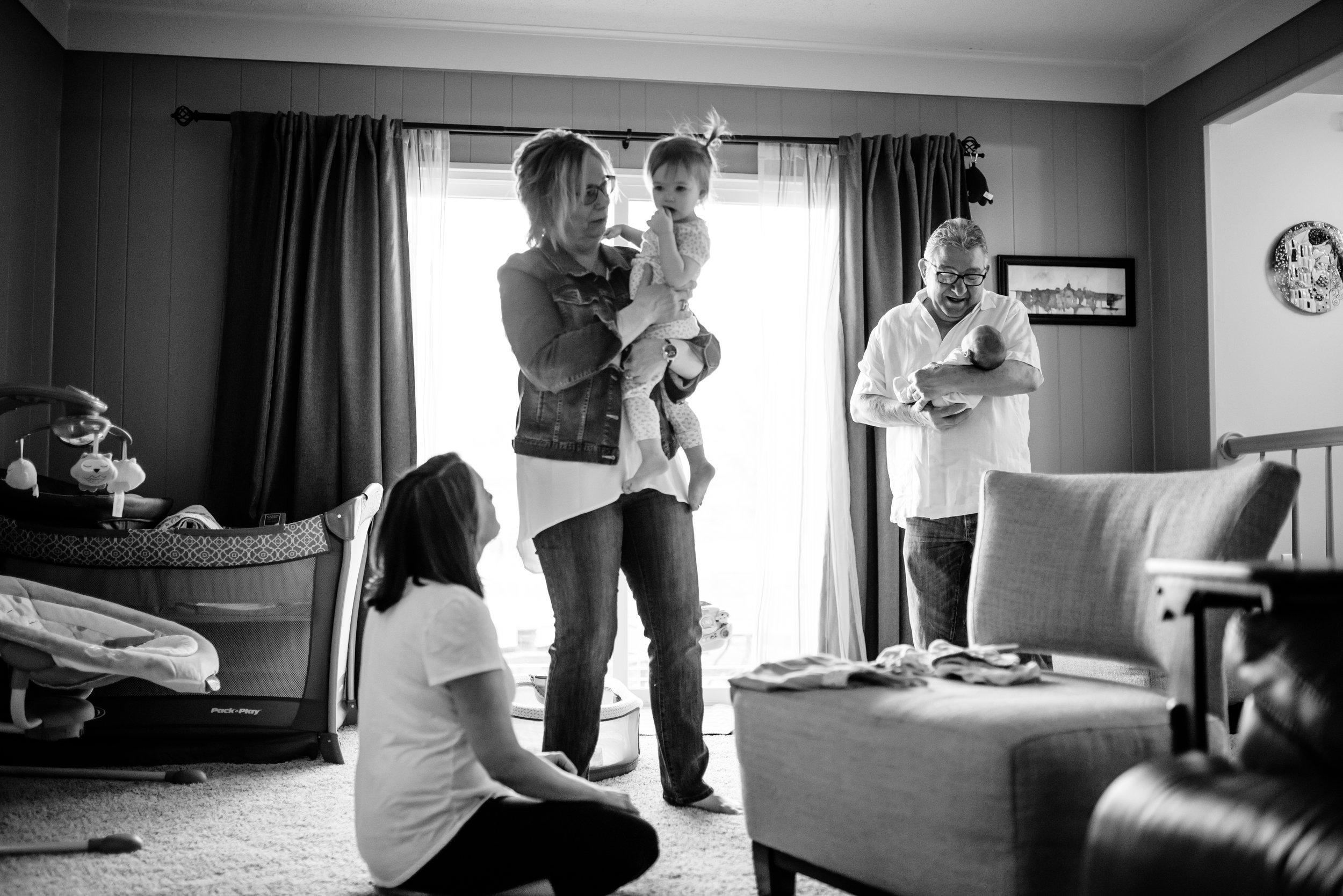 Grandparents hold grandchildren, Mom looks up from floor