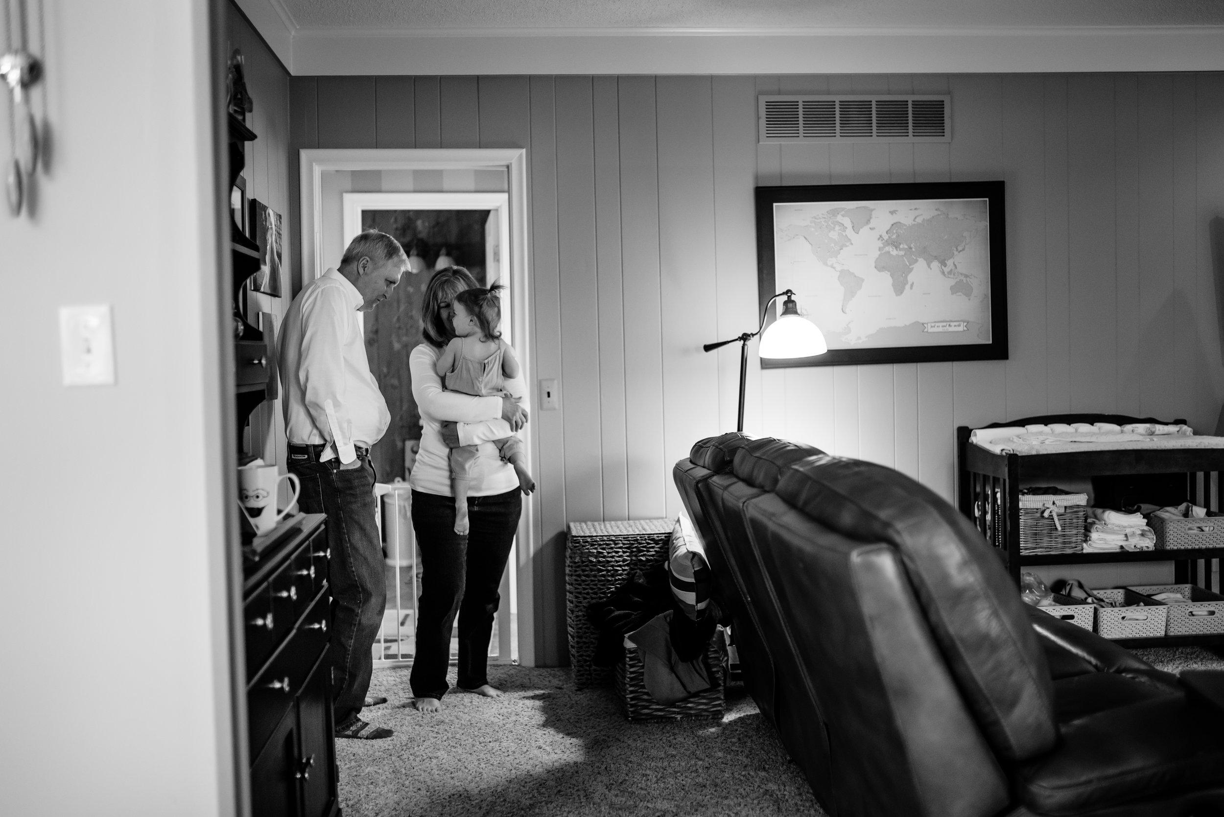 Girl hugs grandmother as grandfather watches
