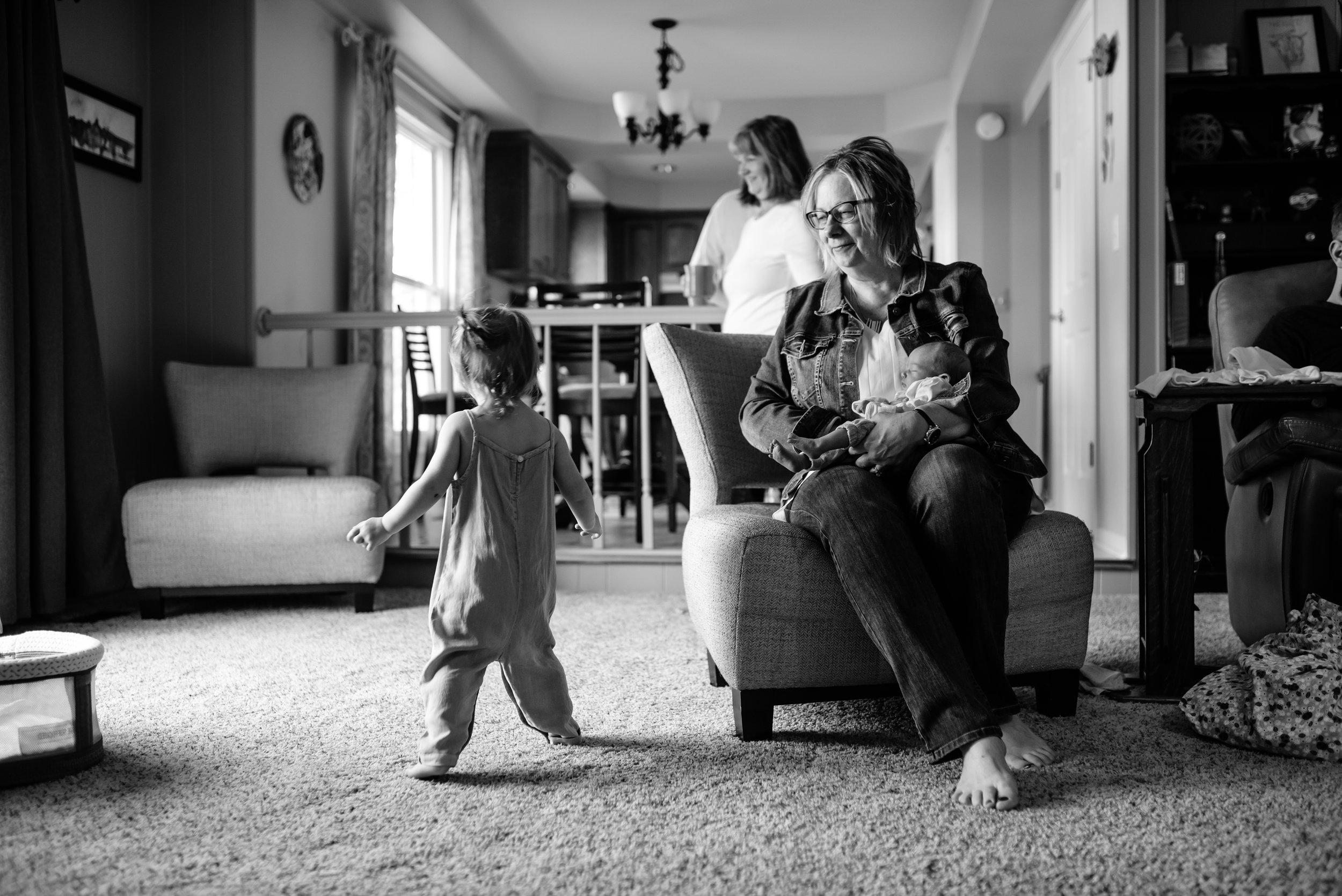 Grandma holds baby and watches girl dance