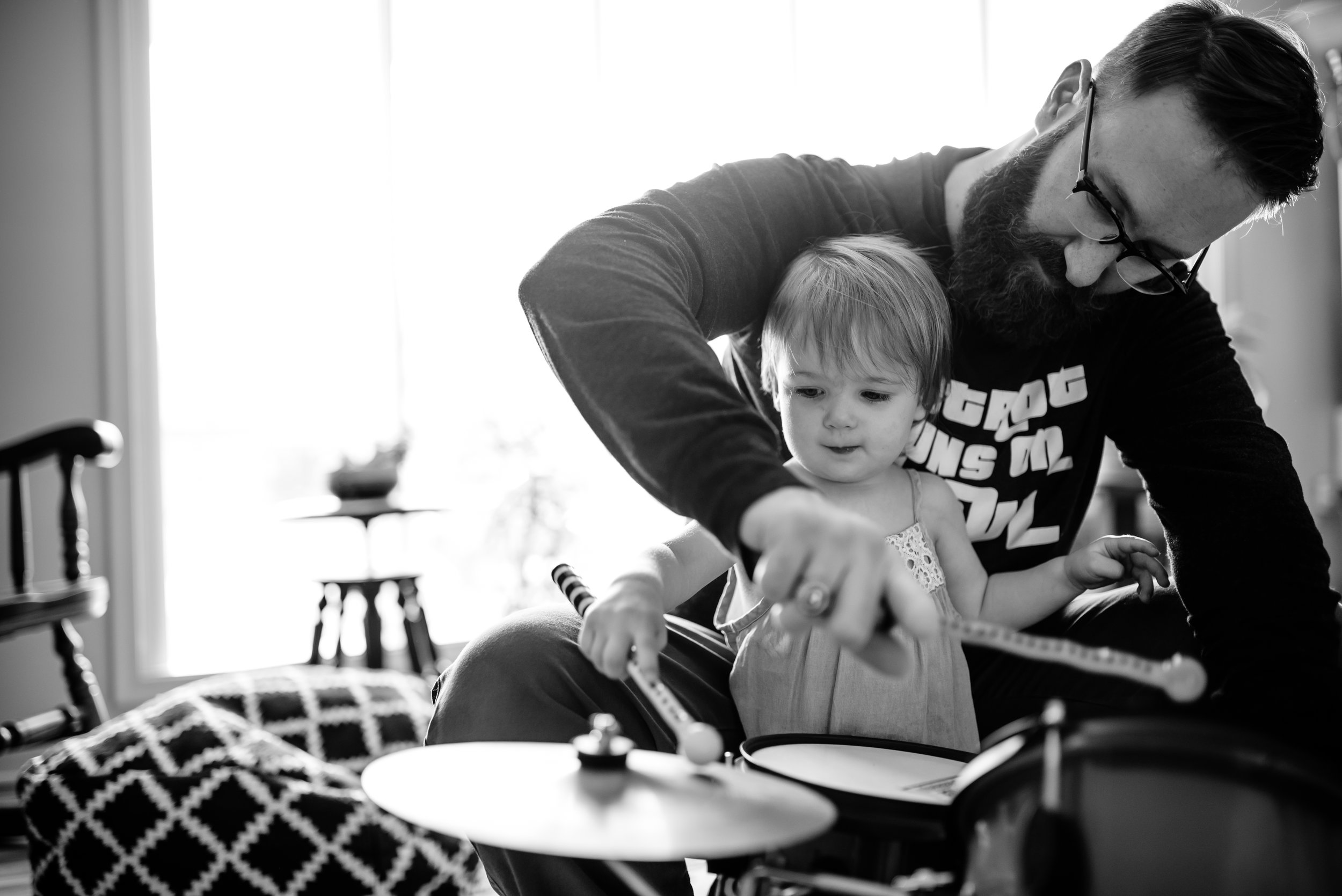 Dad and toddler daughter play drums together