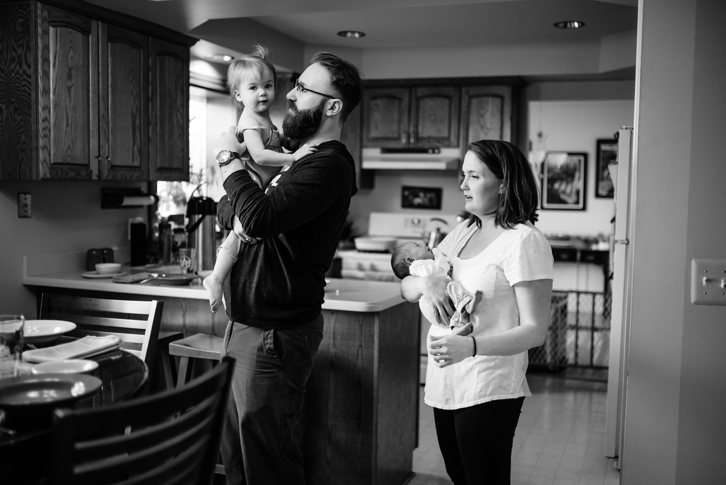 Mom and Dad hold children in kitchen