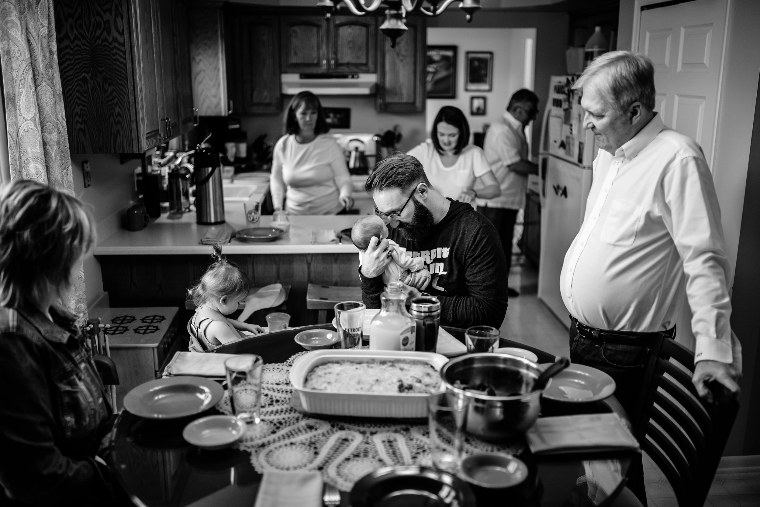 Family gathers for meal in kitchen, Dad has special moment with baby in center of chaos