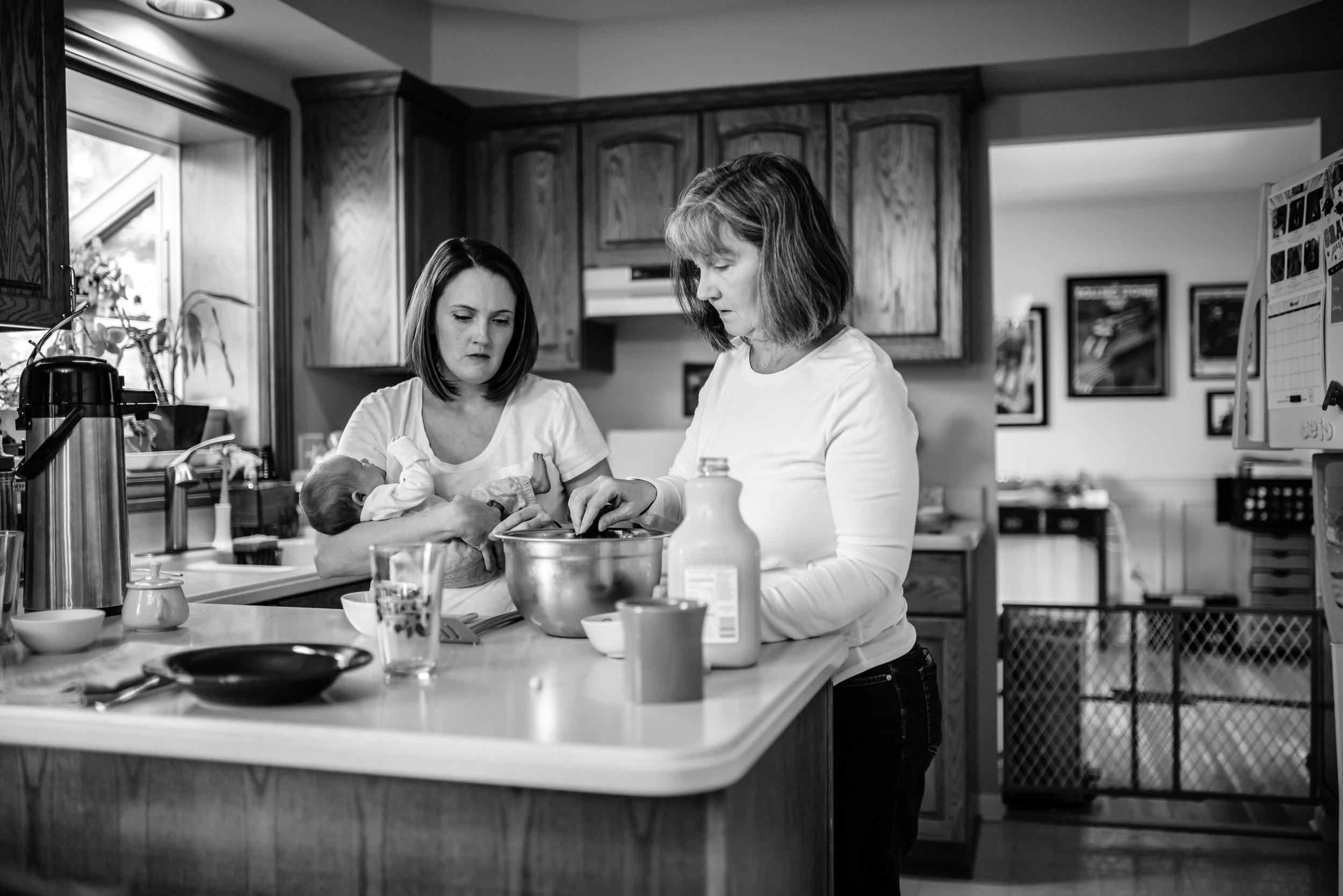 Mom holds baby as she preps breakfast with Grandma