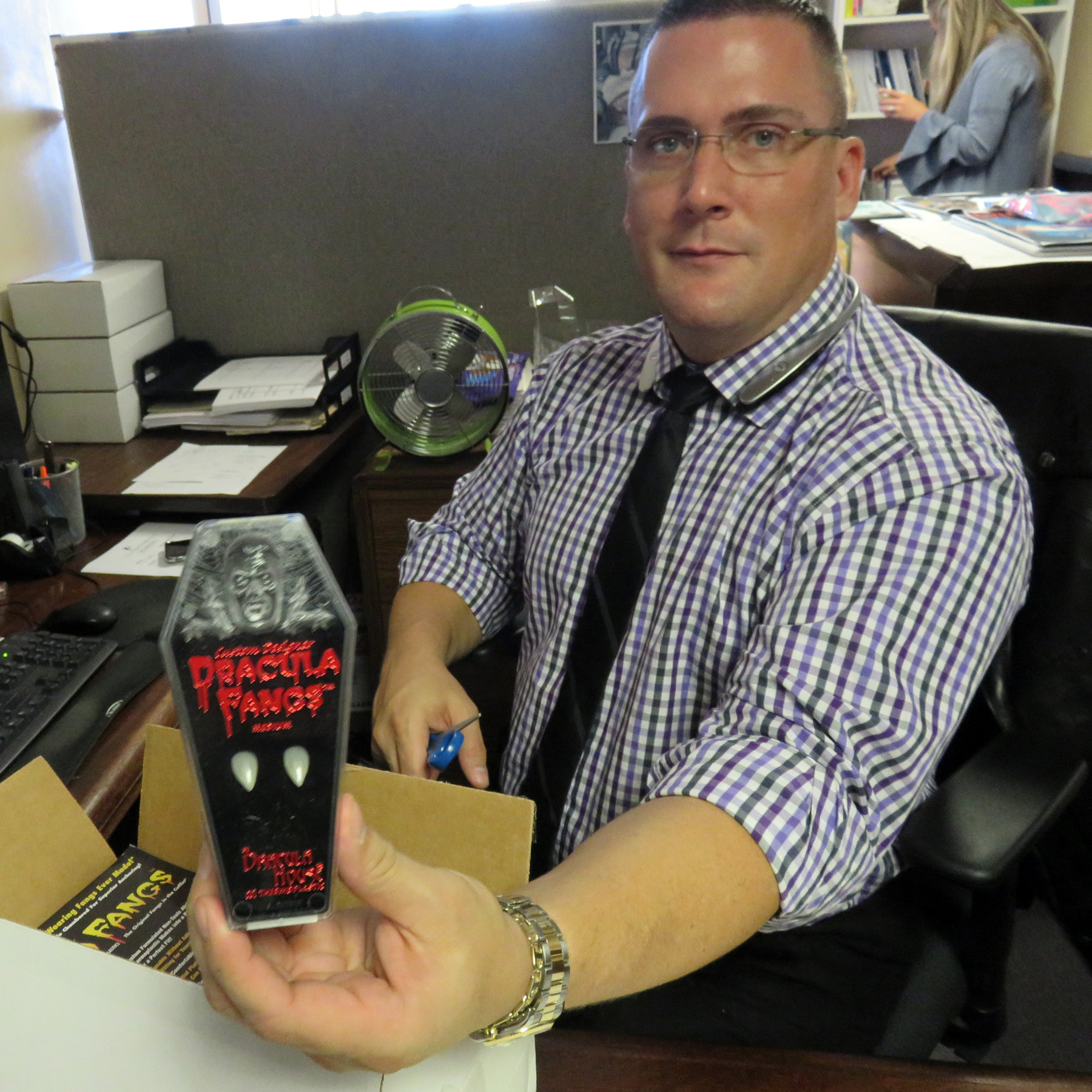 Jason Cobb, Office and Educational Outreach Manager, showing off a package of Dracula fangs.)