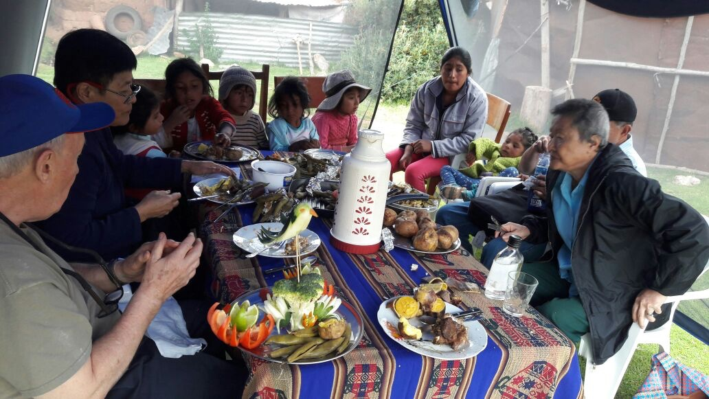 Sharing pachamnca lunch with children at the Pillaray school with customers of Valentin's Pachamama Journeys