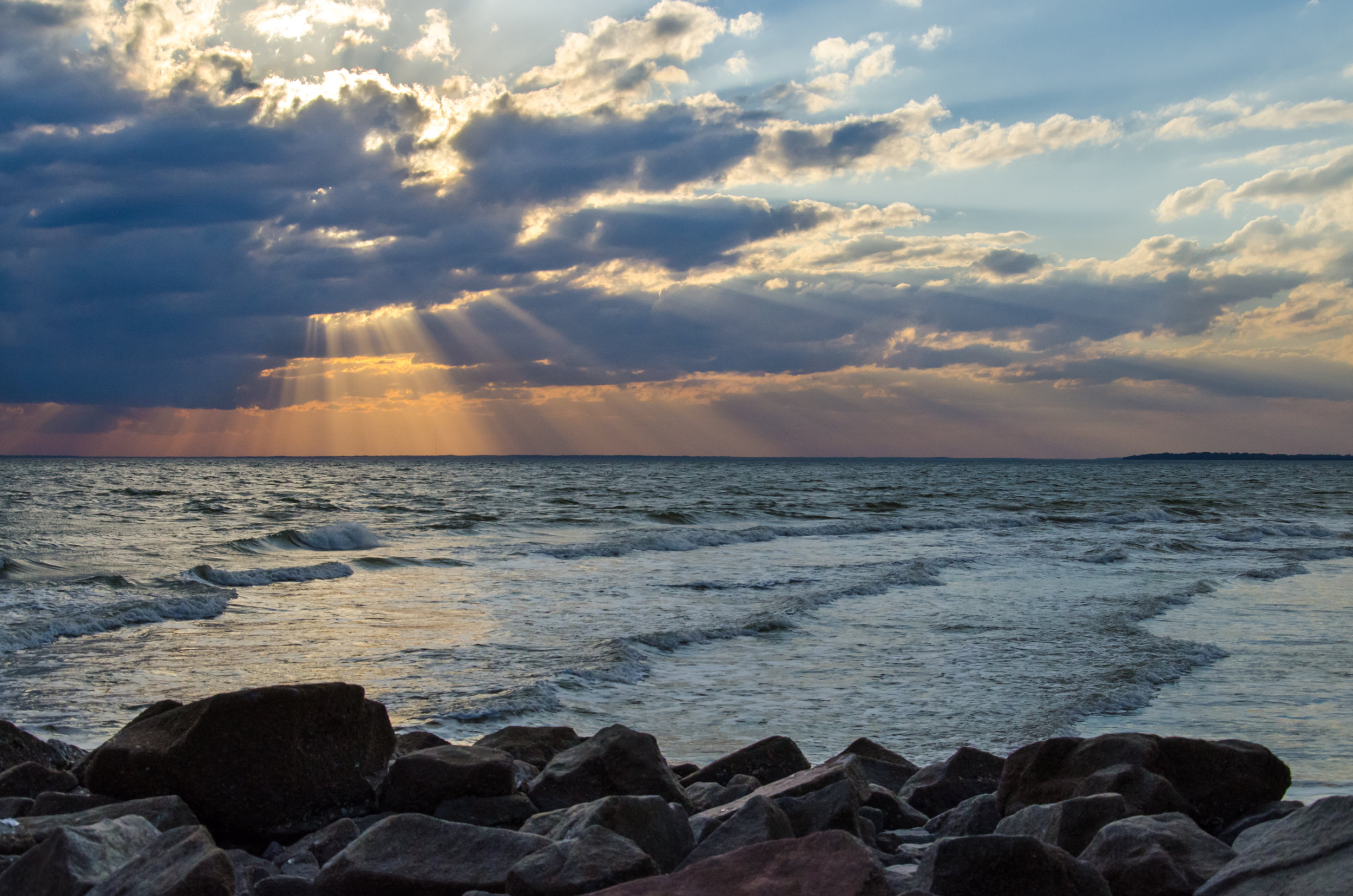 Sun rays beam down through clouds over the ocean.