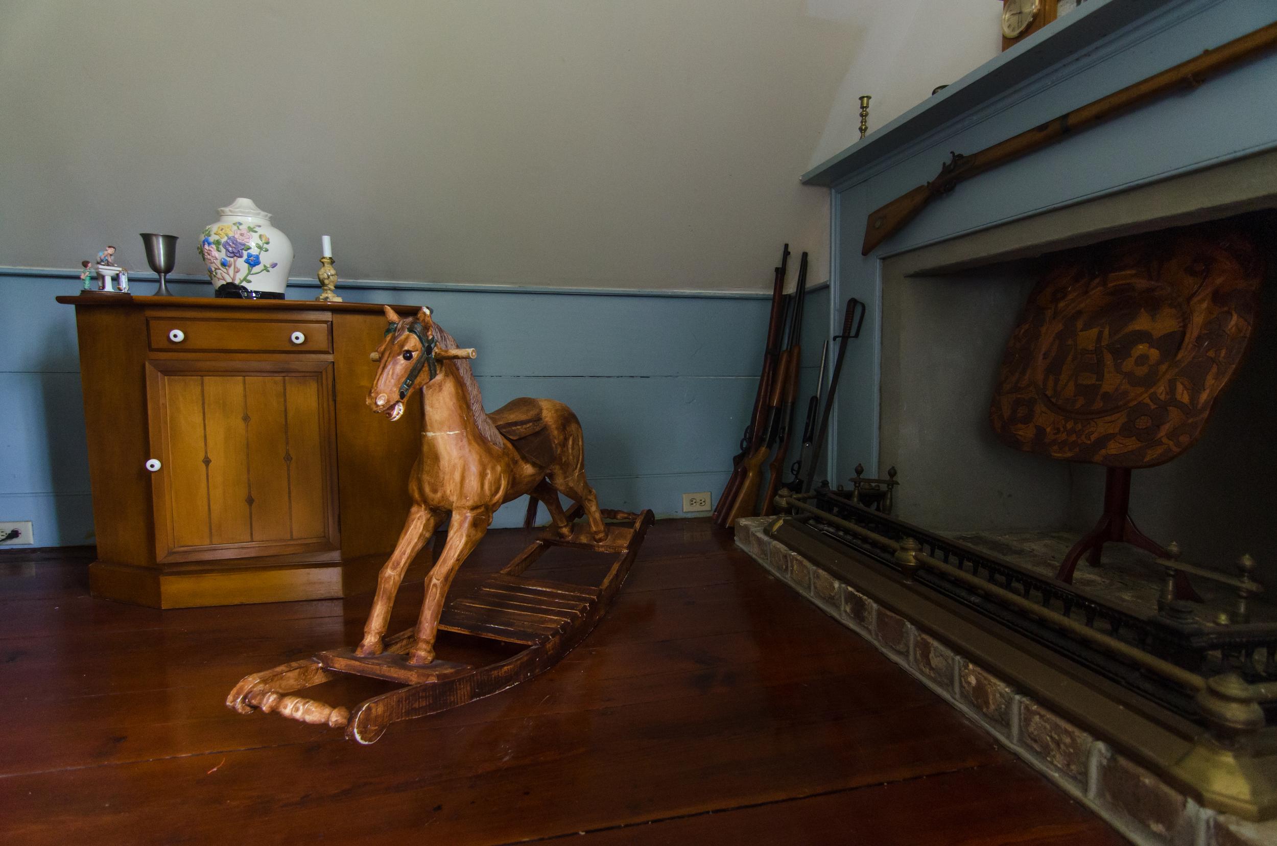 An antique horse-rocker next to a fireplace.